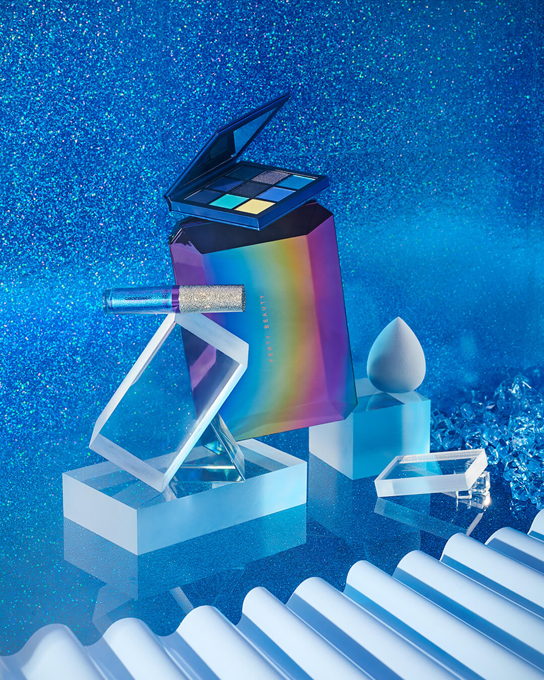 credits: photo - jenna gang, styling - astrid chastka  description: conceptual still life image of fenty beauty and a beauty blender in a cold blue outer space world.