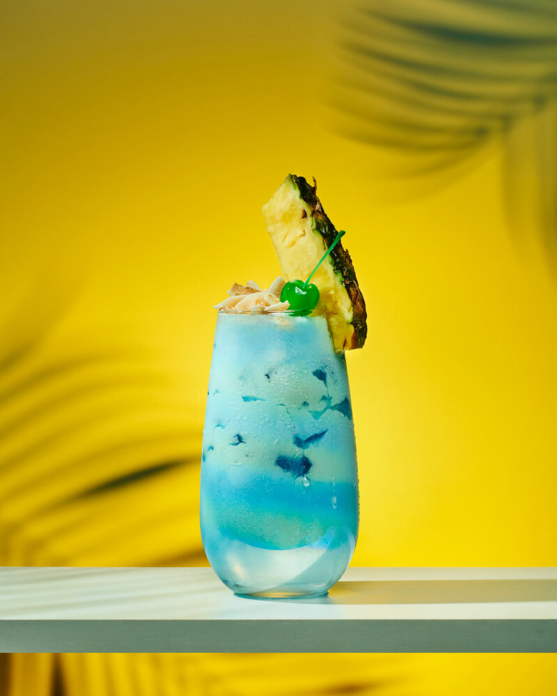 credits: photo- jenna gang, food styling- kristin stangl  description: beverage photograph of blue iced cocktail with pineapple on a yellow background.