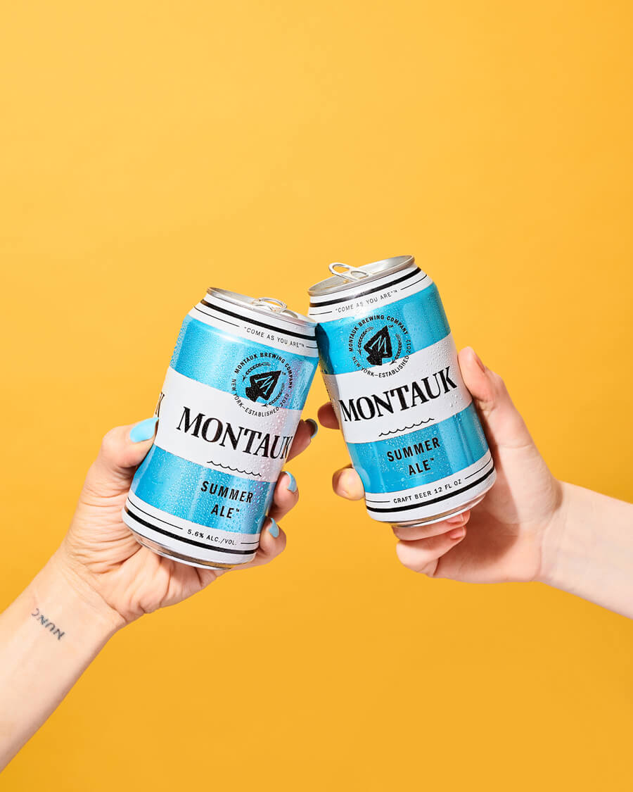 client: refinery29  credits: photo- jenna gang, props- paola andrea, food- ali nardi, direction- megan madden  description: conceptual still life photograph two women cheering their Montauk Summer Ale beers.