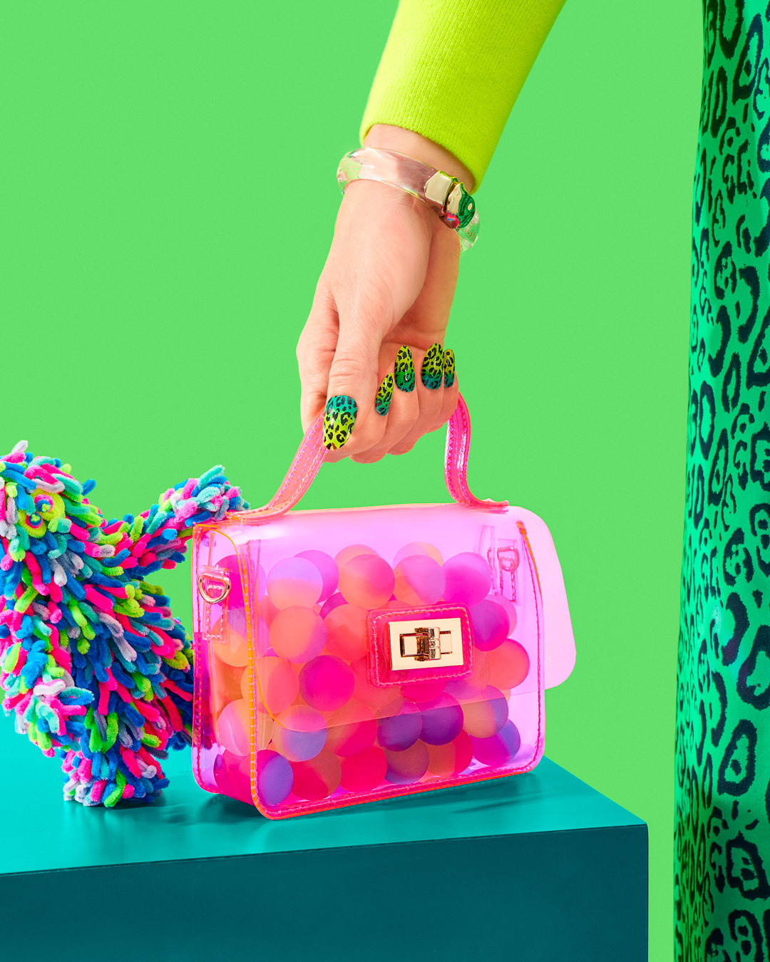 credits: photo - jenna gang, styling - chelsea volpe, nails - natsume chiharu, model - pauline sherrow  description: model wearing a green animal print dress holding a translucent pink handbag filled with colorful balls.