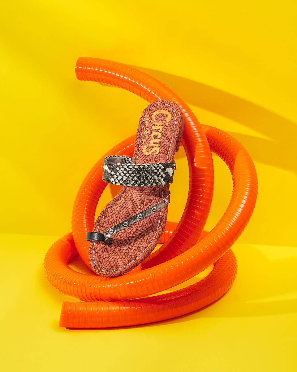 client: circus by sam edelman   credits: photo - jenna gang, styling - anna lemi  description: zebra circus by sam edelman sandals resting on an orange pipe.
