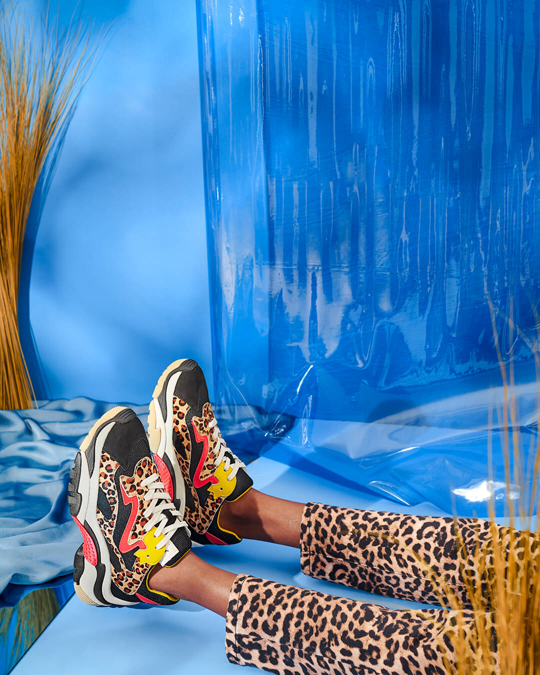credits: photo - jenna gang, wardrobe - ross mccallum, sets - caylah laes  description: model wearing fake zebra shoes and pants on a blue background.