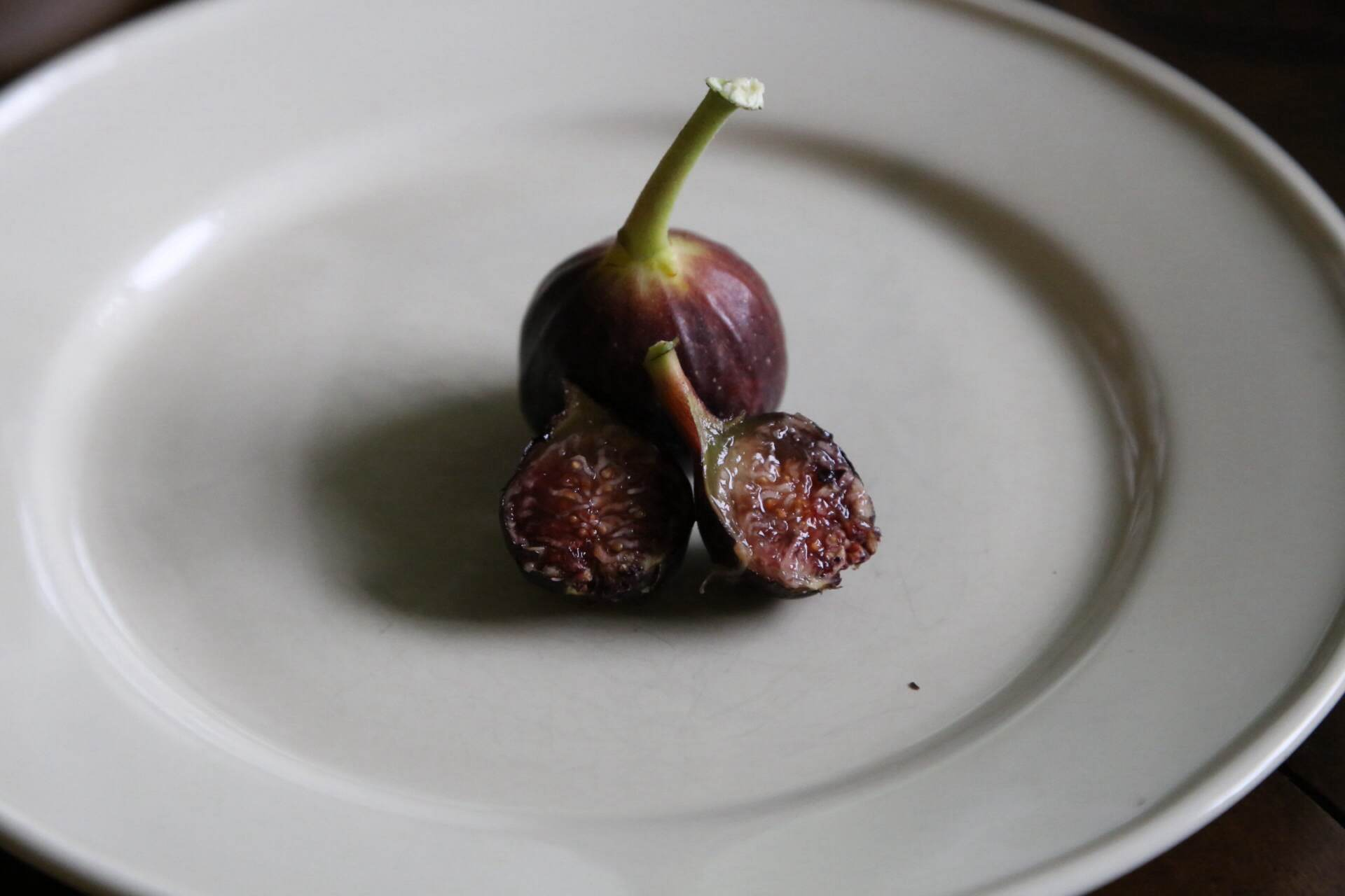 A ripe pair of Ronde de Bordeaux figs on a plate.