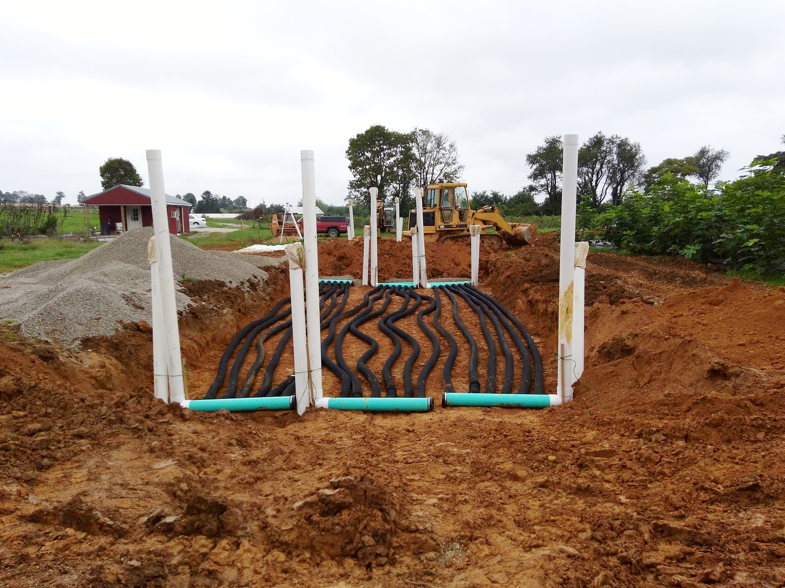 Hole backfilled to 3 feet with the second layer of tubing partially covered. Here you can see the lower risers partially buried. Risers were positioned to allow for tractor entry into the greenhouse.