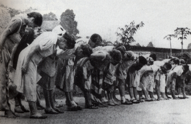 Women bowing to the Japanese flag at a POW camp. 130,000 civillians were interred in Indonesia during WWII.