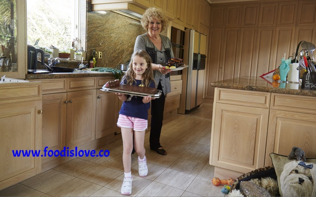 Ruth Scheuer with her grand-daughter Nika carrying the dishes they've prepared in Ruth's kitchen. Nika is very pleased to be in charge of the Nutella wafer cake!