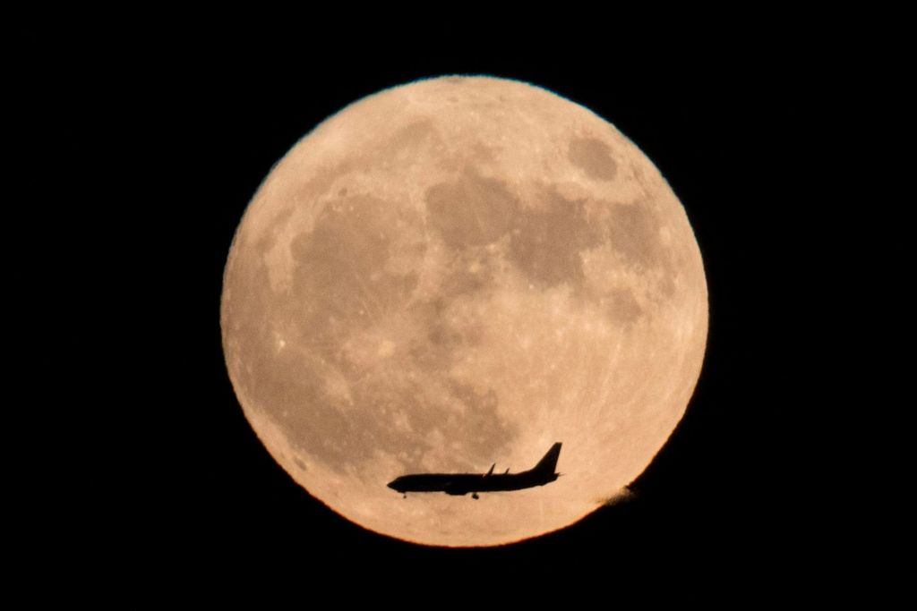 Commercial jet flies across the supermoon this week. (Photo: Ng Hang Guan, AP)