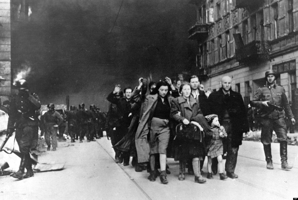 Warsaw Ghetto, May 1943. The sky is black with smoke from burning buildings while captured Jews are moved out for deportation.