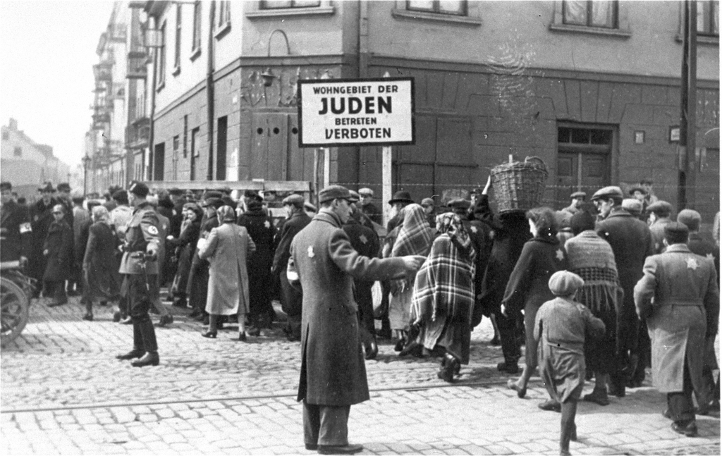 Jews moving into the Lodz Ghetto - known as Litzmannstadt to the Nazis. The sign says that entry to non-Jews is forbidden. (Photo: Bundesarchiv)