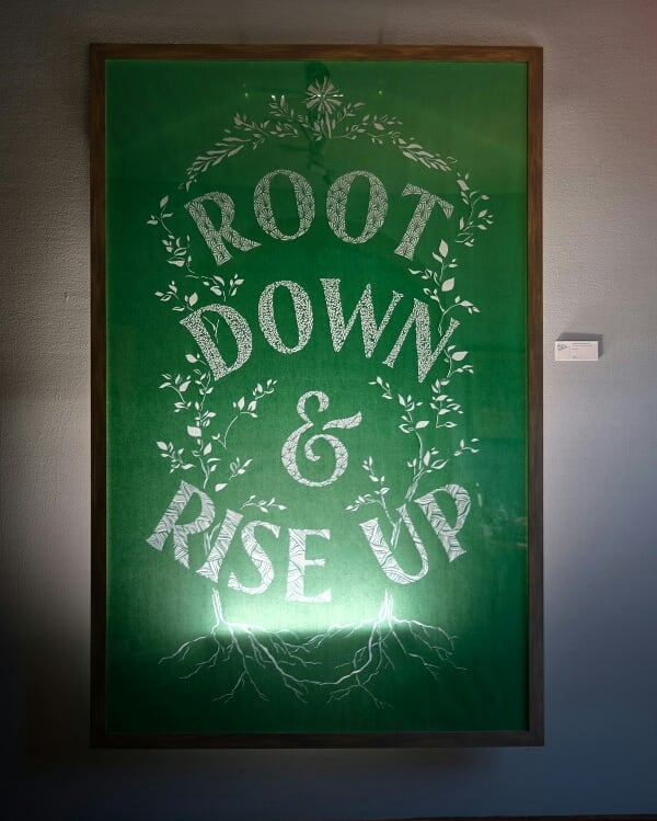 """It's been a long time coming, and finally this large scale handmade papercut piece is framed, lit, and exhibited in a beautiful space. Come see it at @presenttensefitness before summer's end (and consider if you might like to take it home with you!) .... """"Root down & rise up"""" is about choosing to dive deeper into the place where I'm standing - not itching to depart for somewhere """"better"""" but honoring where I am and who I am in order to thrive now, here, in this moment. .... As someone naturally inclined to seek out change and newness, this continues to be a tough mindset to cultivate. .... Spending about 60 meditative hours making tiny scalpel papercuts helped, though."""