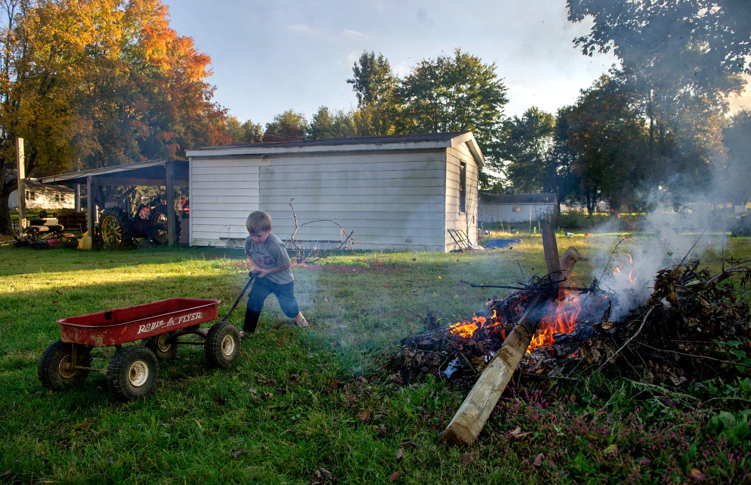 Jayden Patterson of Booneville, 5, collects sticks to burn in a fire at his home in Booneville, Ind. Thursday, Oct. 17, 2014.