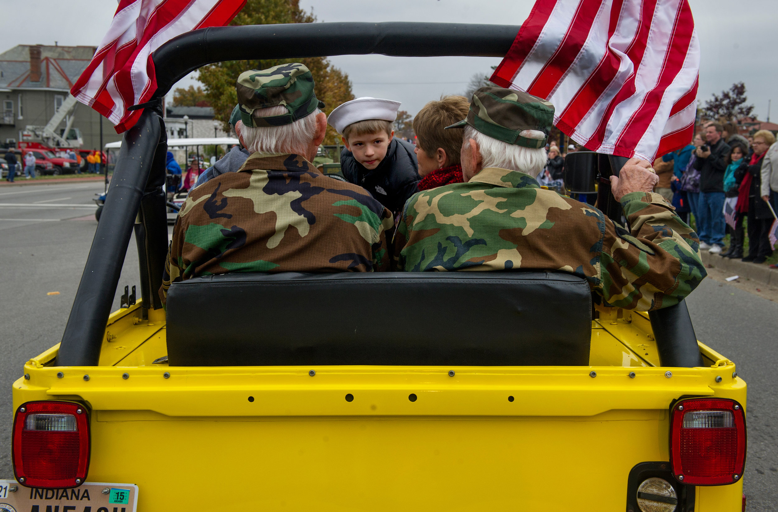 World War II Army veterans and brothers Dwayne Hume (left) and Donald Hume (right) ride with Joey Langerak, 7, of Evansville in a 1978 Jeep during the Veterans' Day Parade in on Riverside Drive in Evansville Saturday, Nov. 8, 2014.