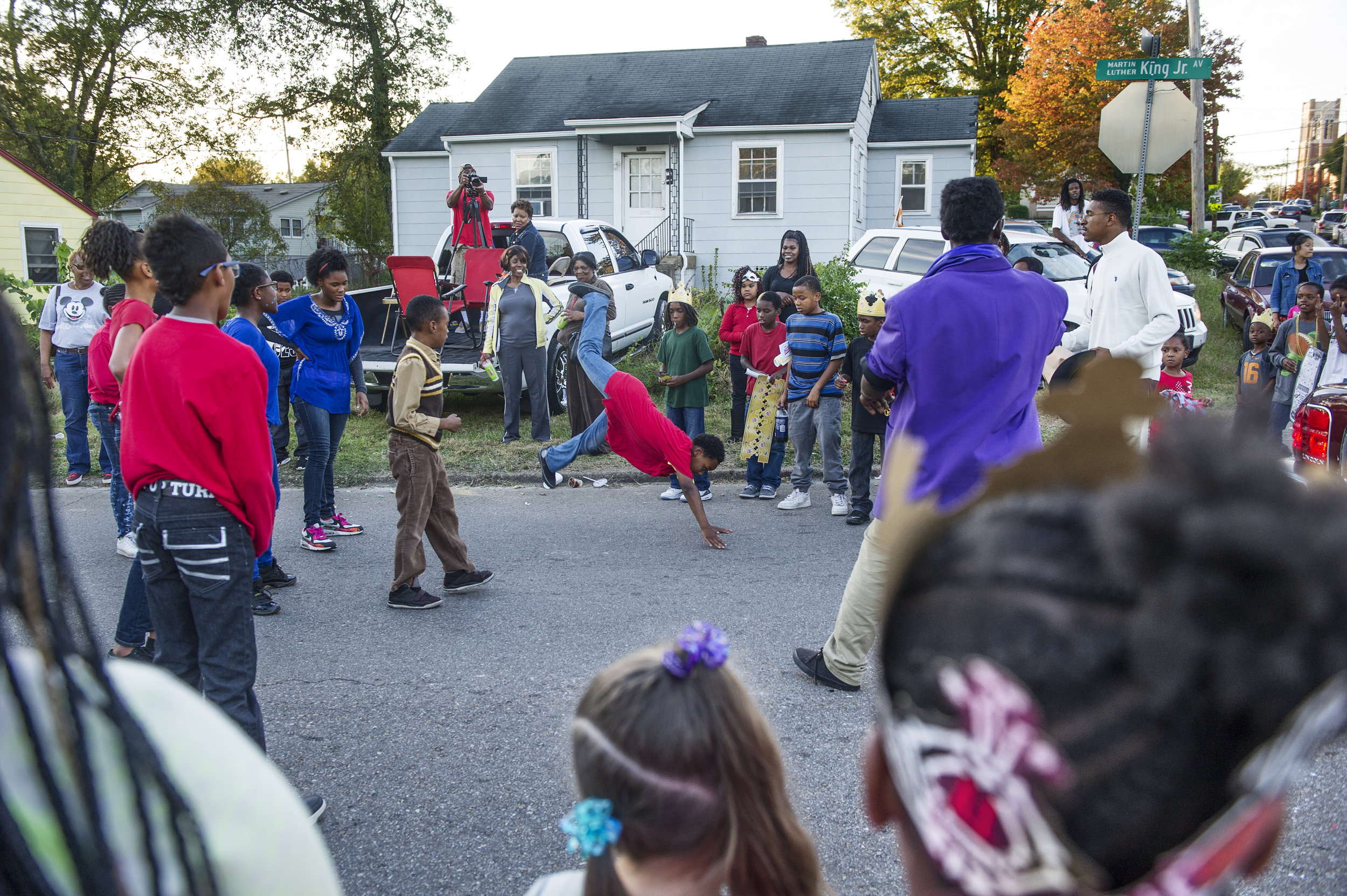 Parade goers watch Presean Brown, 10, (center) dance during the Divine Urban Expression Dream Team's performance at the Austin East high school homecoming parade Friday, Oct. 23, 2015.