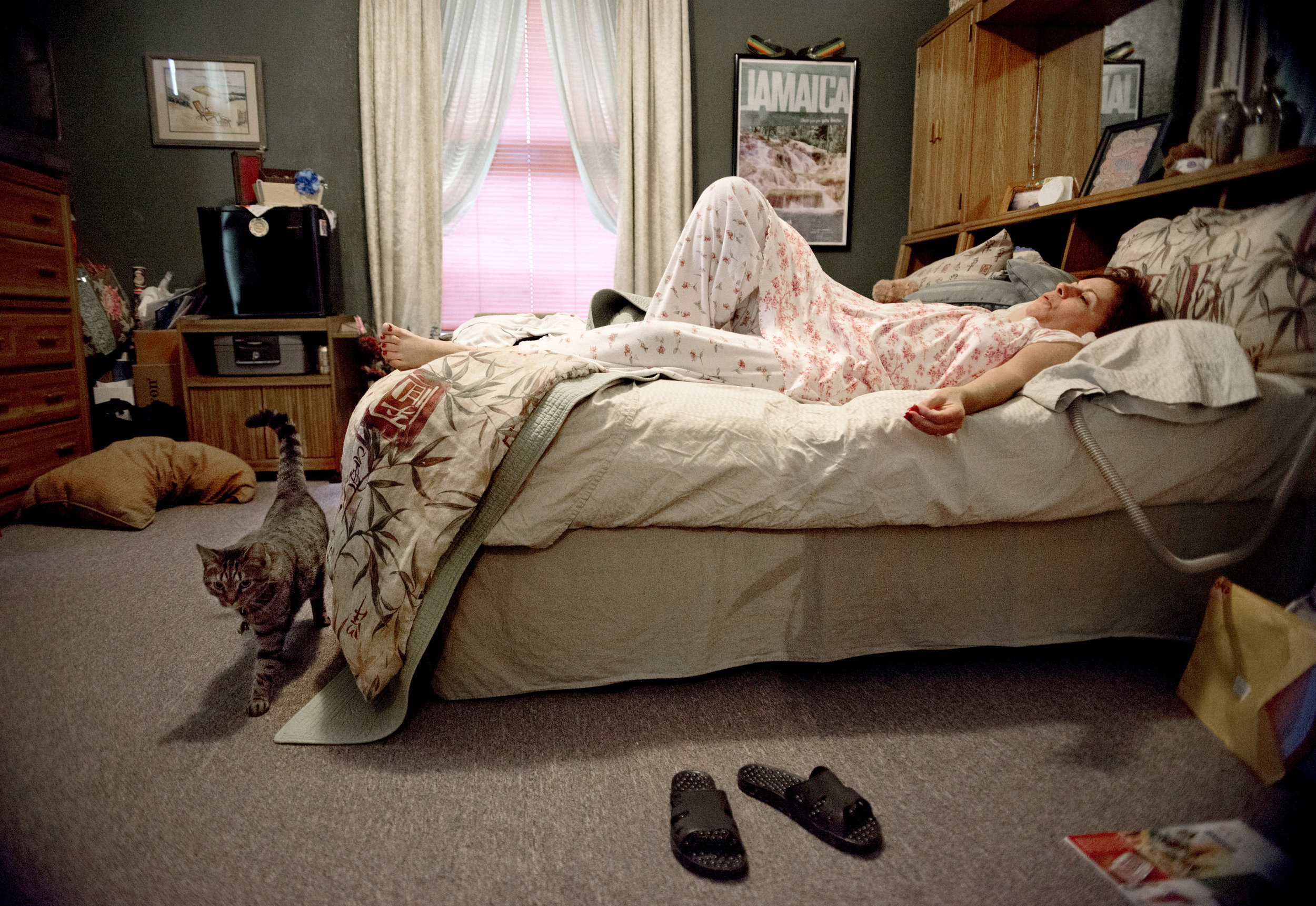 Gayle Ayala lies in her bed in her apartment at the Hospitality House in Chester Ill. on her day off from the four jobs she works. She moved 850 miles from Fairfax, Va. to Chester, Ill.  to be near her husband, David Ayala, who was an inmate at Tamms Correctional Center, a Maximum Security prison, until he was transferred to a prison in Nevada (where he and Gayle now live) in Chester, Ill. Gayle and David met through inmate essay-writing program, Tamms Year 10. She fell in love with him in May of 2009, and the couple was engaged Jan. 1, 2010. She quit her job as a legal secretary, where she was earning nearly six figures, and moved to Chester. Through the Hospitality House Gayle has found comfort in meeting other women married to men with long-term or life sentences. She describes it as a sisterhood.