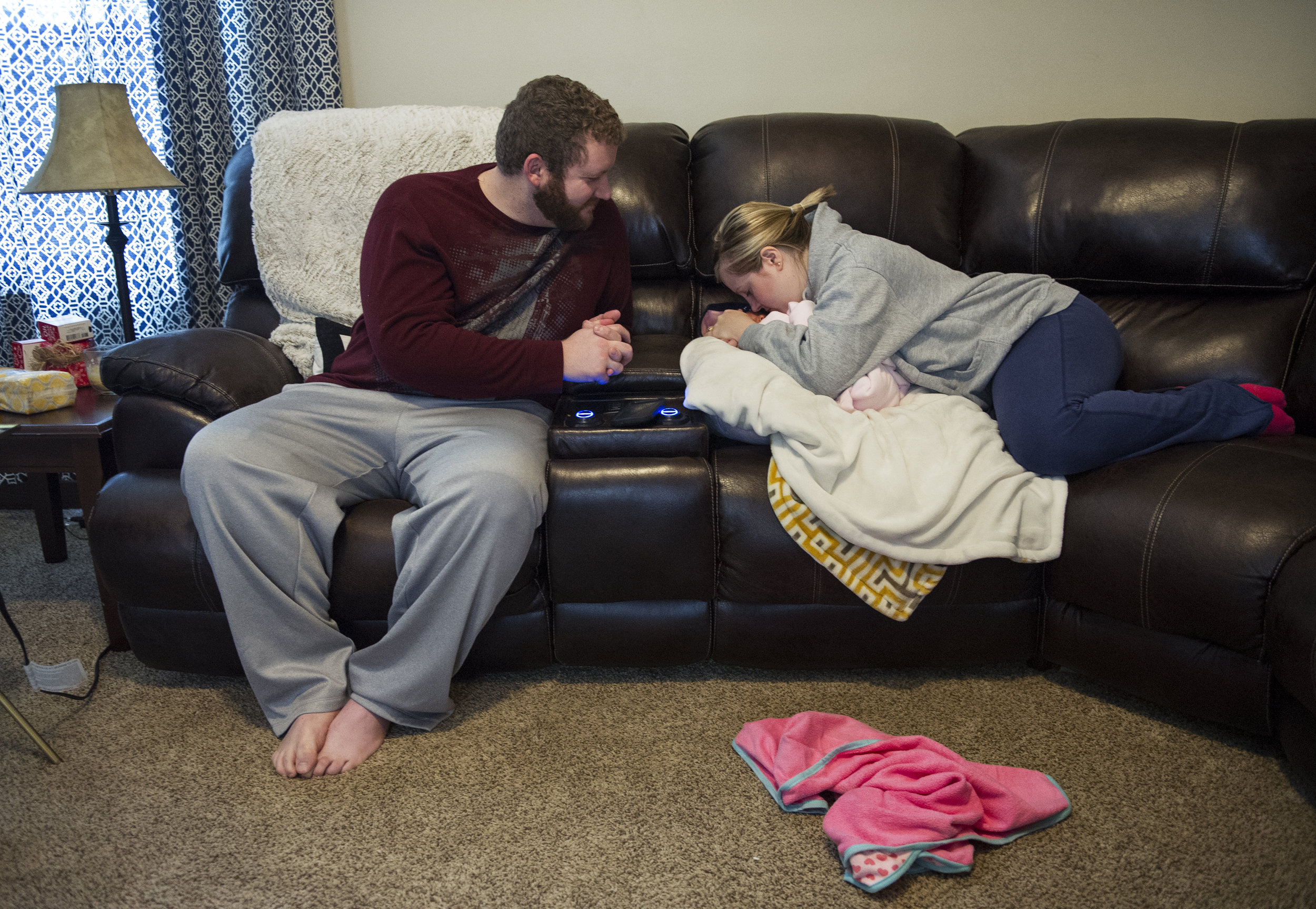 """Michael and Erickia gush over Gracelyn at their home in Evansville Thursday Dec. 11, 2014. Since they brought her home they have spent their time enjoying getting to know her and showing her off to their friends and relatives. """"My heart is overflowing with love,"""" Erickia said."""