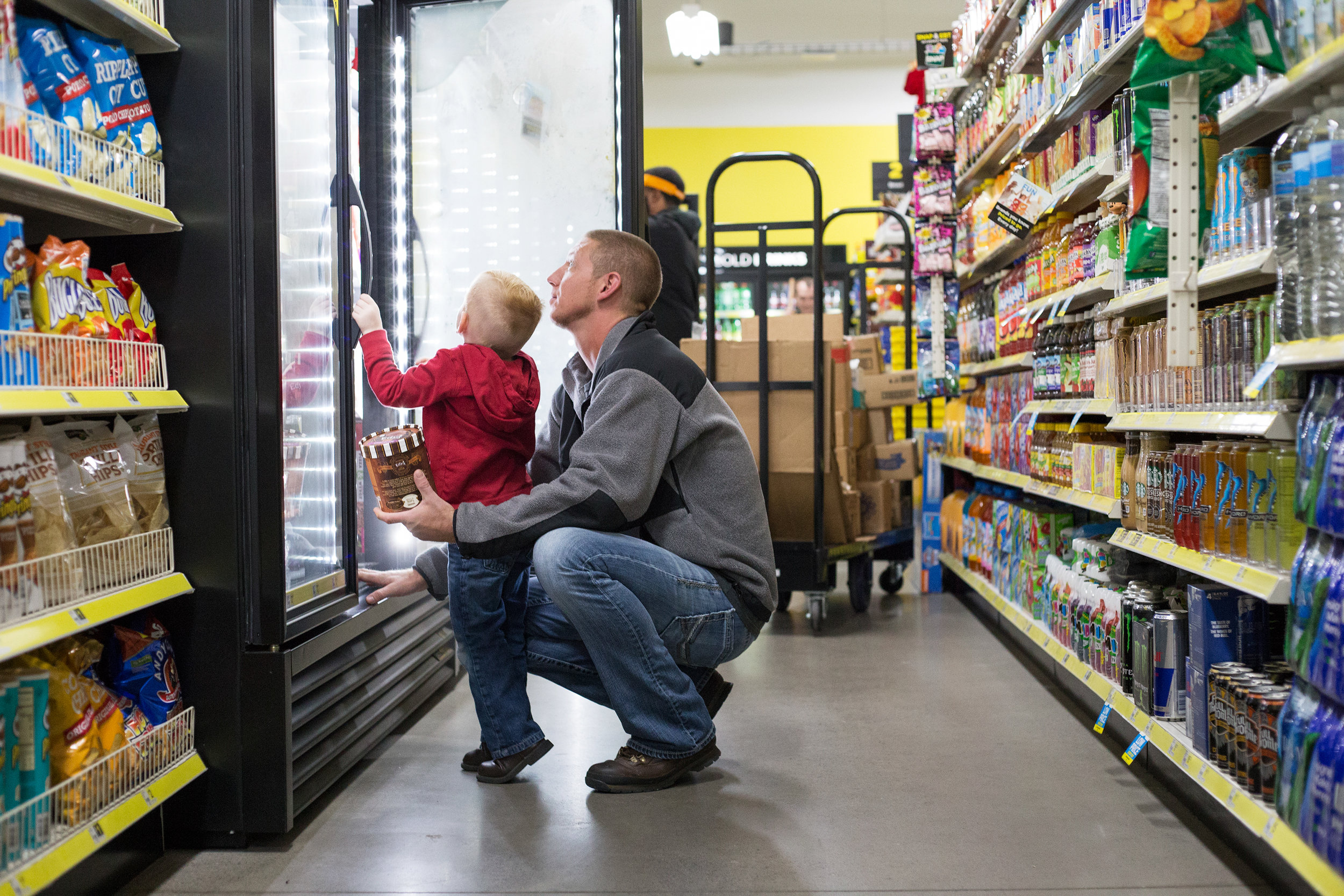 Dalton Cranfield, 3, and his father David Cranfield decide which flavor of ice cream they will purchase at Dollar General in Evensville, Tenn. Thursday, Nov. 16 2017. David said they don't shop at the store often, but when they do it is for the convenience.