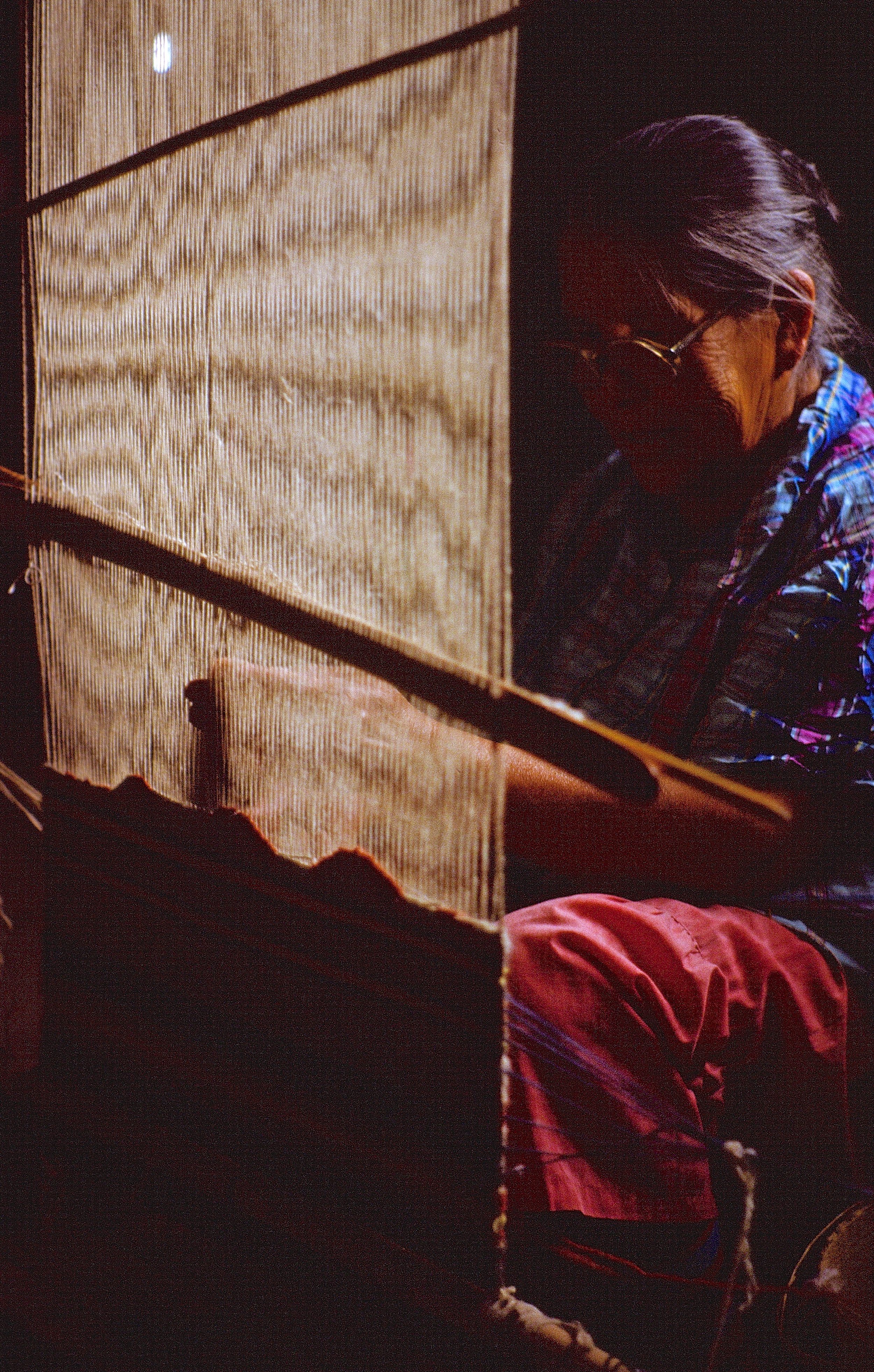 Mabel Woodman weaving by the light of a kerosine lamp and a wood stove (1984-85)