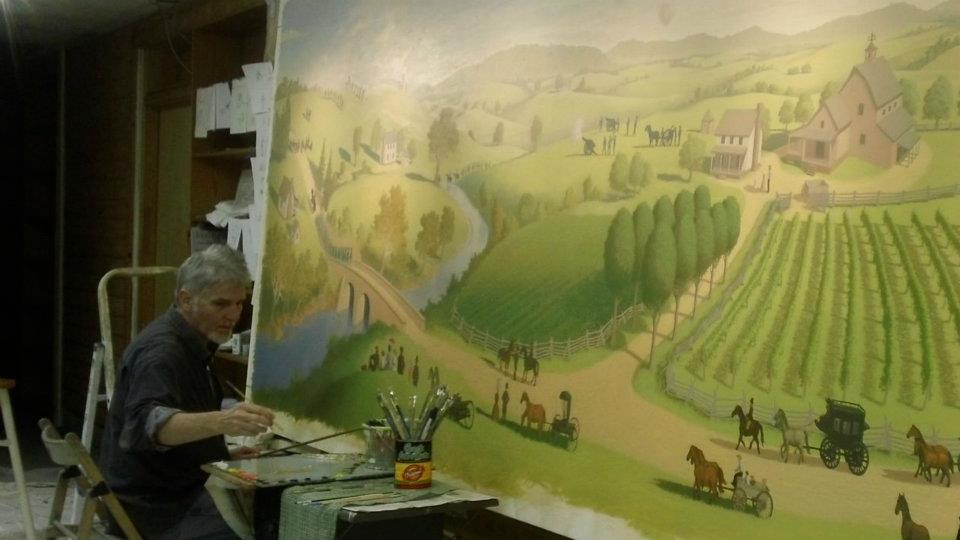 The artist working on the Bull Run Winery Mural.