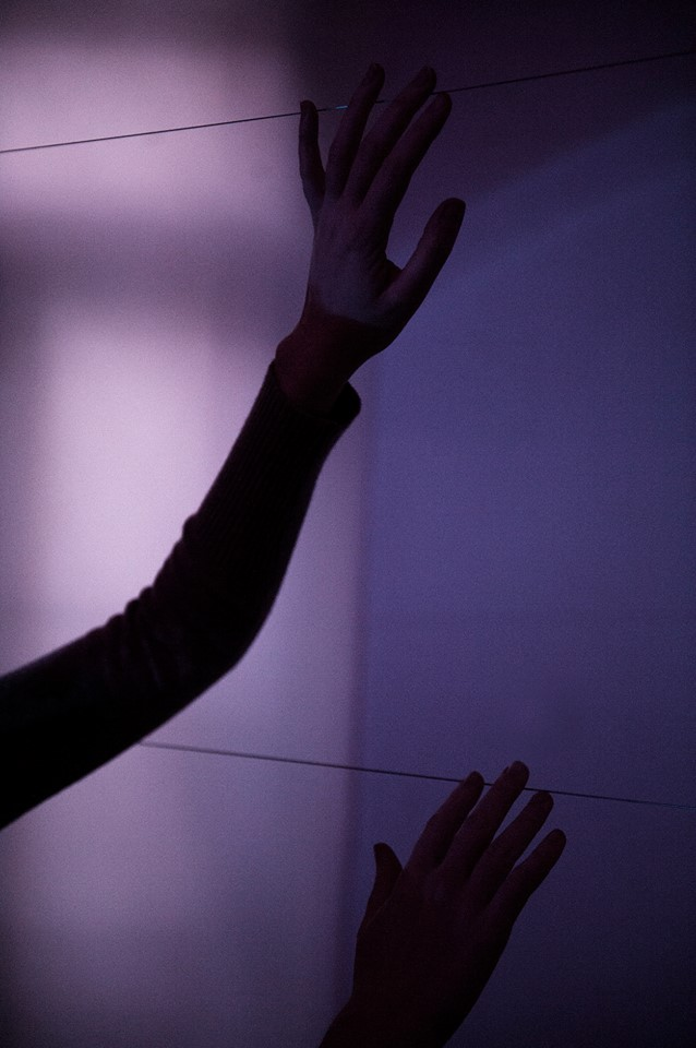 Detail of installation room 1. Hands on piano strings, light diffusion paper.  Photo by Stéphane Charpentier.