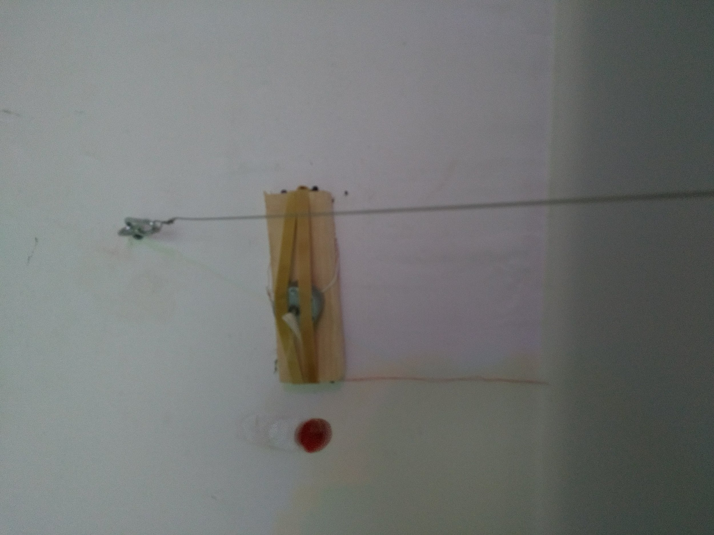 Detail of room 1: motion activated motor attached to found wood with rubber bands, found piano felt.