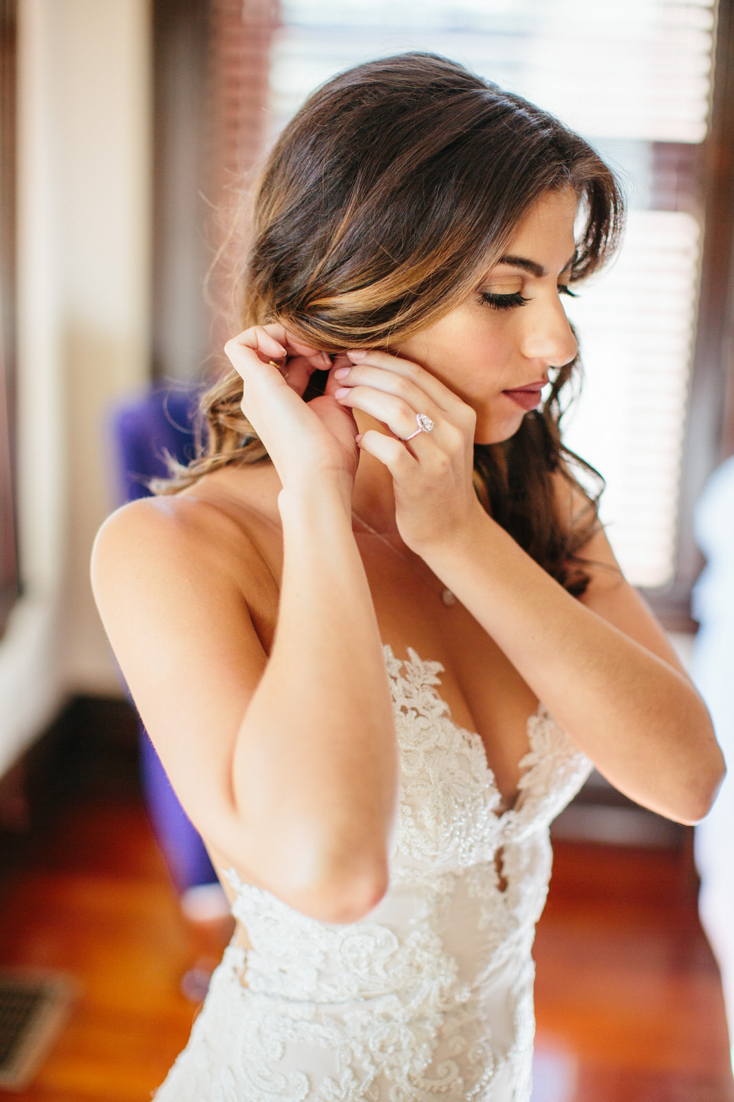 Bride putting on earrings Armature Works Tampa
