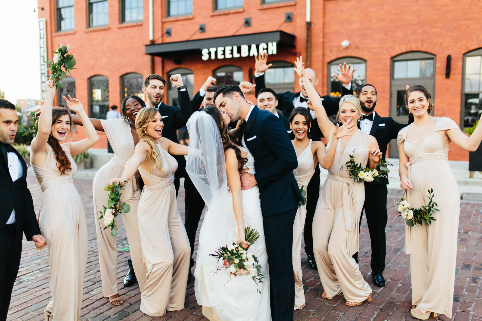 Bridal Party Cheering Bride and Groom Kiss