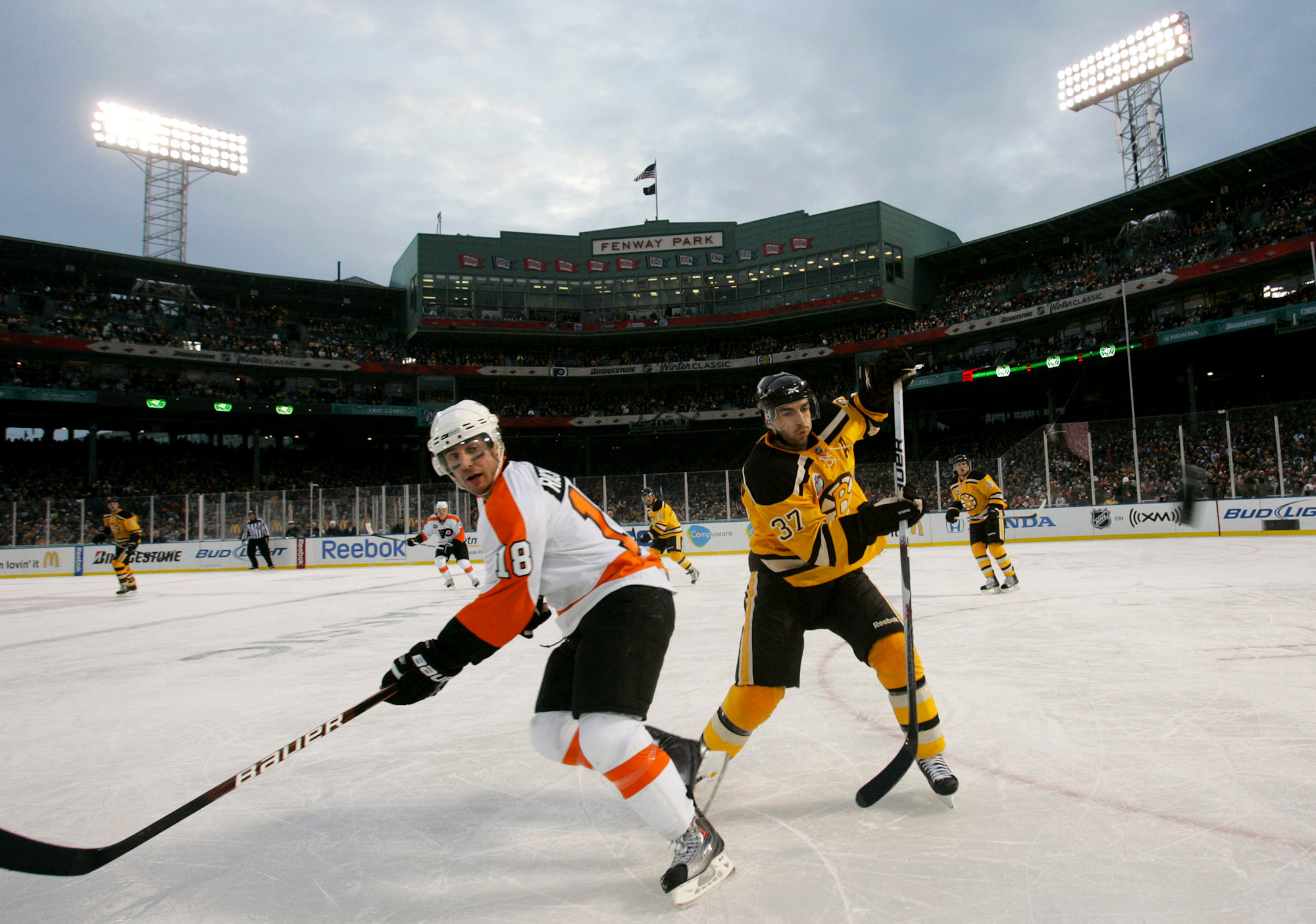 Boston Bruins center Patrice Bergeron (37) and Philadelphia Flyers center Mike Richards (18) chase down a loose puck in the third period of the 2010 Bridgestone NHL Winter Classic at Fenway Park in Boston, Massachusetts on New Years Day, January 1, 2010. The Bruins defeated the Flyers 2-1.