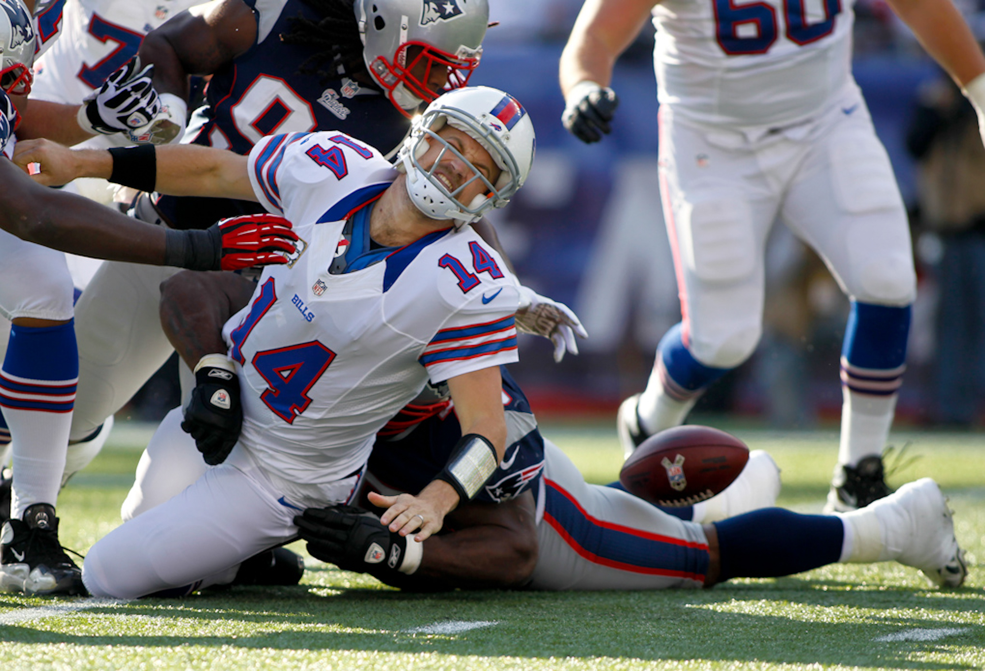 Buffalo Bills quarterback Ryan Fitzpatrick (14) fumbles the ball as he is sacked by New England Patriots defensive lineman Vince Wilfork in the first quarter at Gillette Stadium in Foxboro, Massachusetts on November 11, 2012.