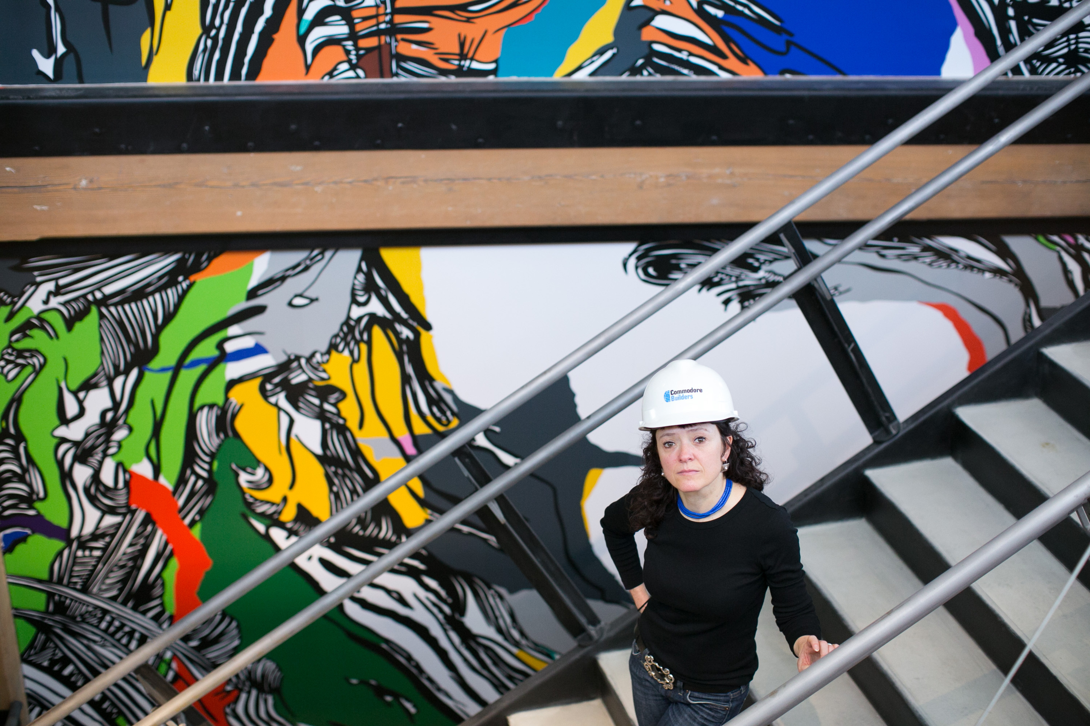 03/12/2015 - Mural artist Sophia Ainsley poses with her piece titled 'In Person, 574' which is being installed in the renovated 574 Boston Avenue on Thursday, March 12, 2015. (Matthew Healey for Tufts University)