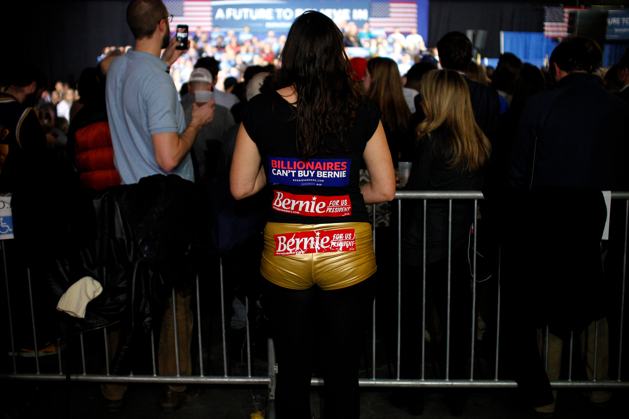 A supporter of Democratic presidential candidate Bernie Sanders watches from the back of the room as the candidate addresses the crowd at a Super Tuesday rally at the Champlain Valley Exposition in Essex Junction, Vermont on March 1, 2016.