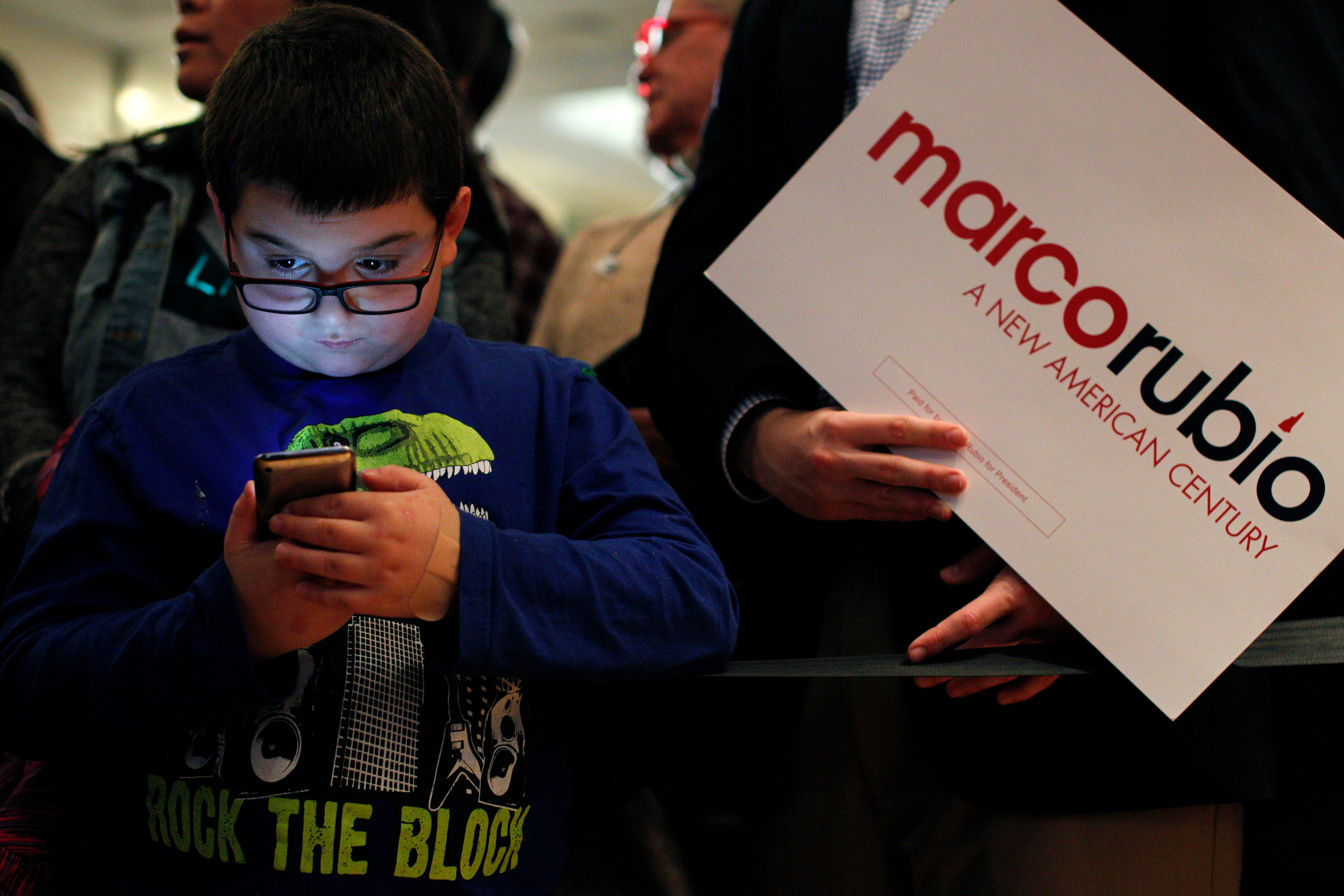 Mark Mooers, 9 of Manchester, New Hampshire, plays a game on his iPod while waiting with his family at a primary night watch party for Republican candidate for president Marco Rubio at the Radisson in Manchester, New Hampshire on February 9, 2016. Early results showed Rubio finishing in fifth place in the nations first Presidential Primary.