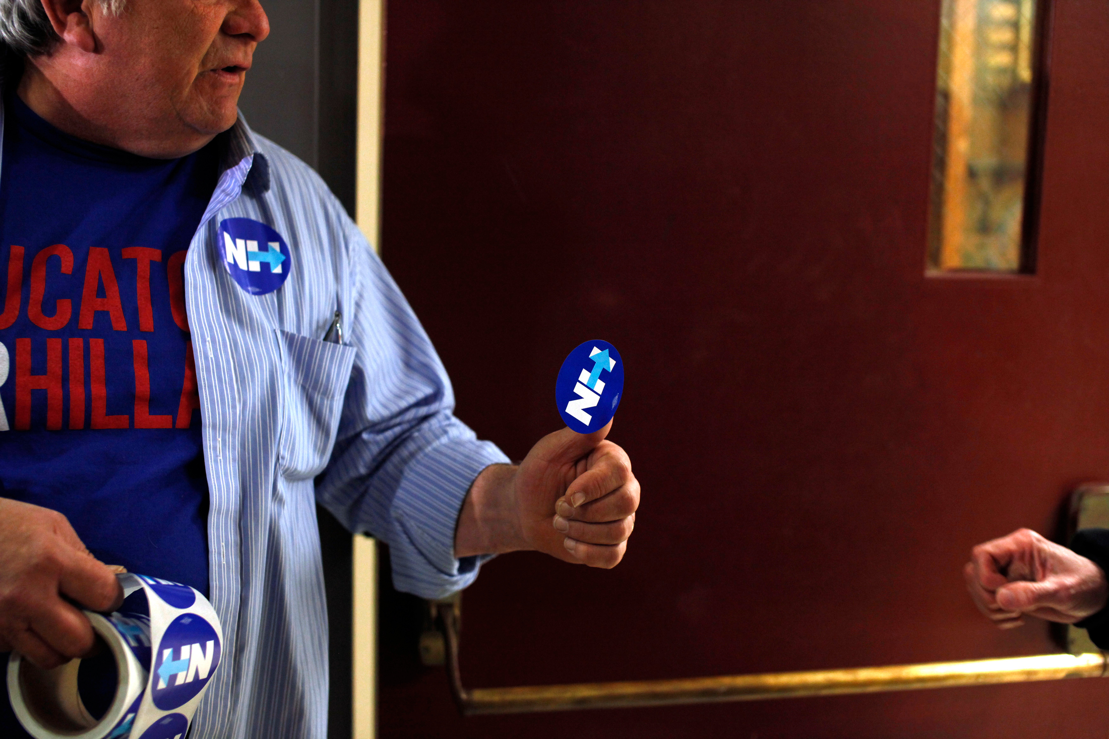 James Mills (L) a volunteer for Democratic presidential candidate Hillary Clinton, hands out stickers before a Get Out The Vote rally at Alvirne High School in Hudson, New Hampshire on February 8, 2016. The event is Hillary Clinton's final pitch to potential voters before the New Hampshire Primary on Tuesday.