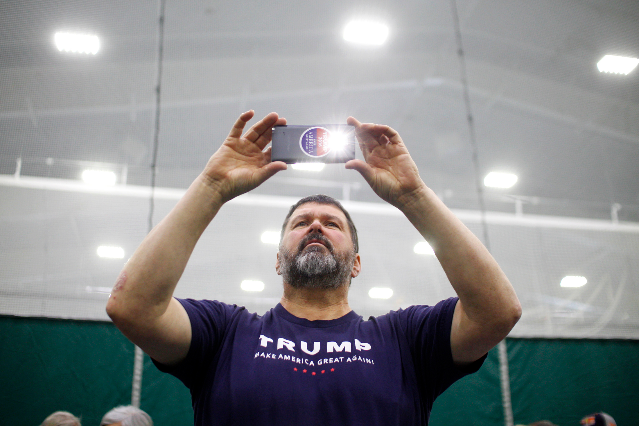 Donald Trump supporter Donald Ostie of Colebrook, New Hampshire takes a photo of the stage prior to a rally for Republican candidate for president Donald Trump at Plymouth State University in Holderness, New Hampshire on February 7, 2016. New Hampshire will hold the first primary in the nation on February 9th.