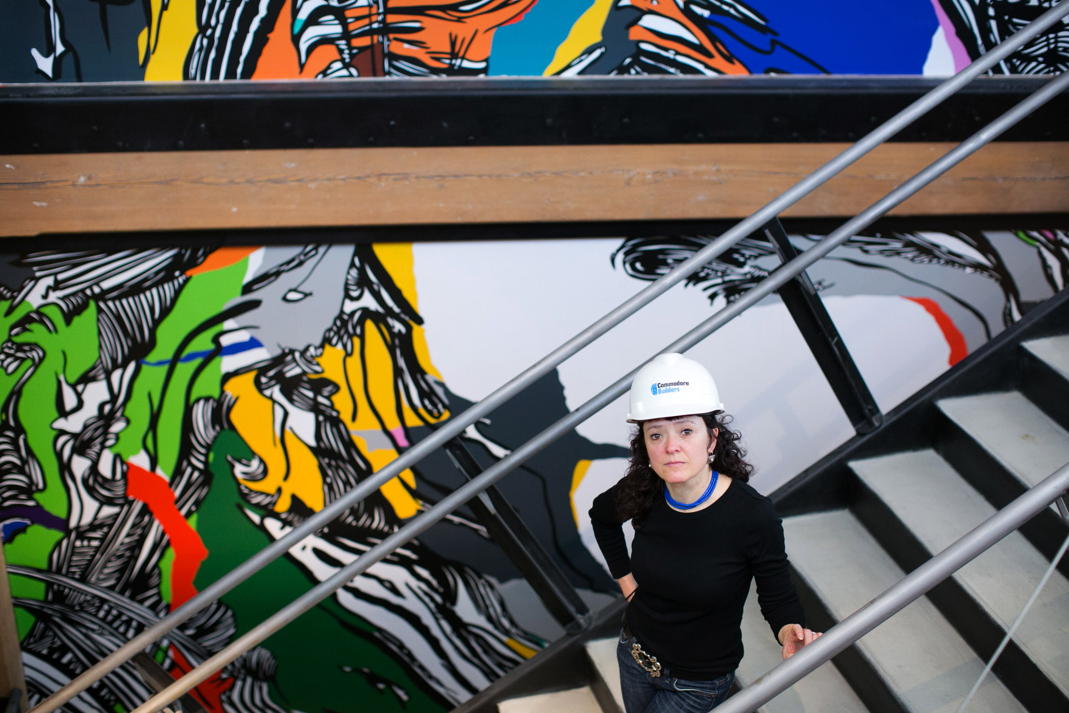 Mural artist Sophia Ainsley poses with her piece titled 'In Person, 574' which is being installed in the renovated 574 Boston Avenue in Medford, Massachusetts on Thursday, March 12, 2015.