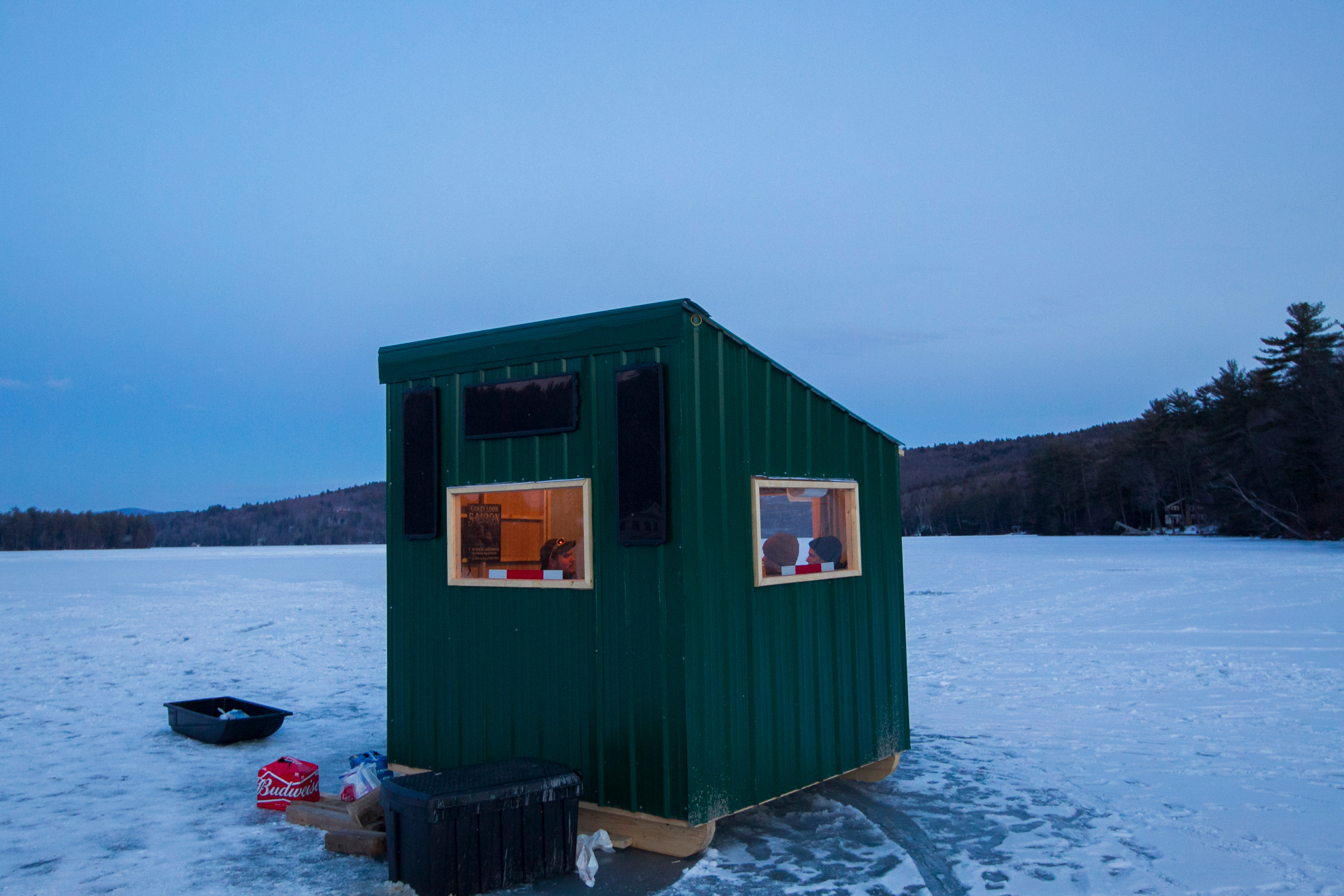 New Hampshire resident Duncan Wentworth (L) hangs  out in a friends ice fishing bob house on Little Squam Lake in Ashland, New Hampshire on February 7, 2016. New Hampshire will hold the first in the nation primary on February 9th.