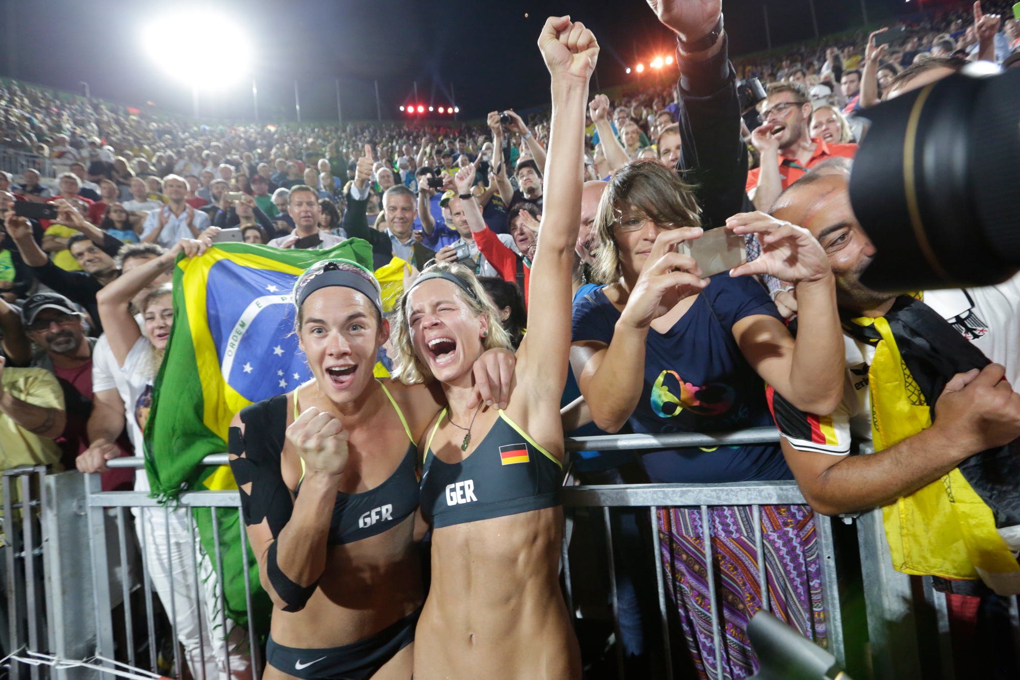 Laura Ludwig and Kira Walkenhorst of Germany celebrate with fans after winning the gold medal in their Beach Volleyball Women's Gold medal match against Agatha Bednarczuk Rippel and Barbara Seixas de Freitas of Brazil at the Beach Volleyball Arena at the 2016 Rio Summer Olympics in Rio de Janeiro, Brazil, on August 17, 2016.
