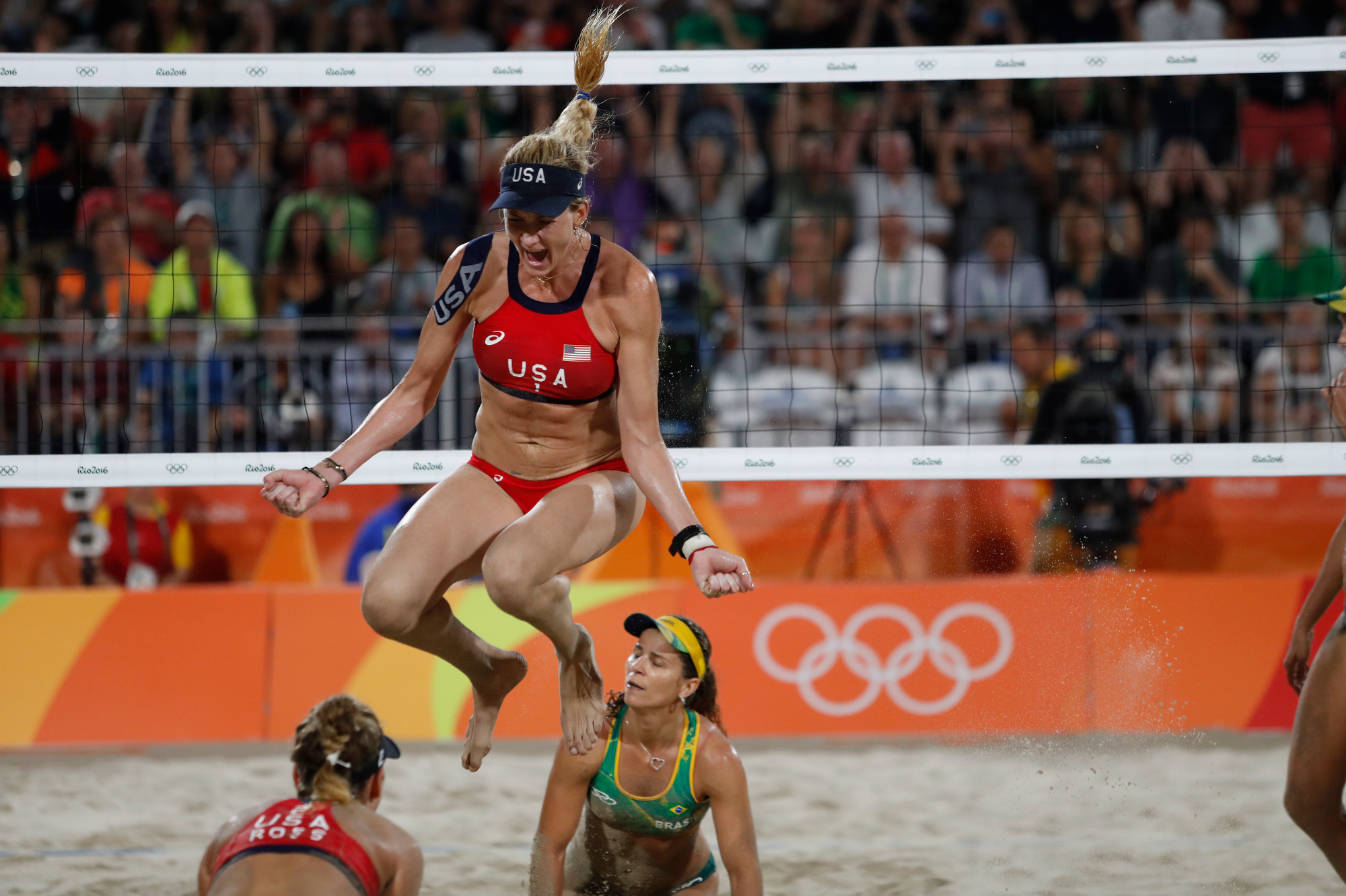 Kerri Walsh Jennings of the United States leaps in the air and celebrates in the Beach Volleyball Women's Bronze medal match against Larissa Franca Maestrini and Talita Rocha of Brazil at the Beach Volleyball Arena at the 2016 Rio Summer Olympics in Rio de Janeiro, Brazil, on August 17, 2016.