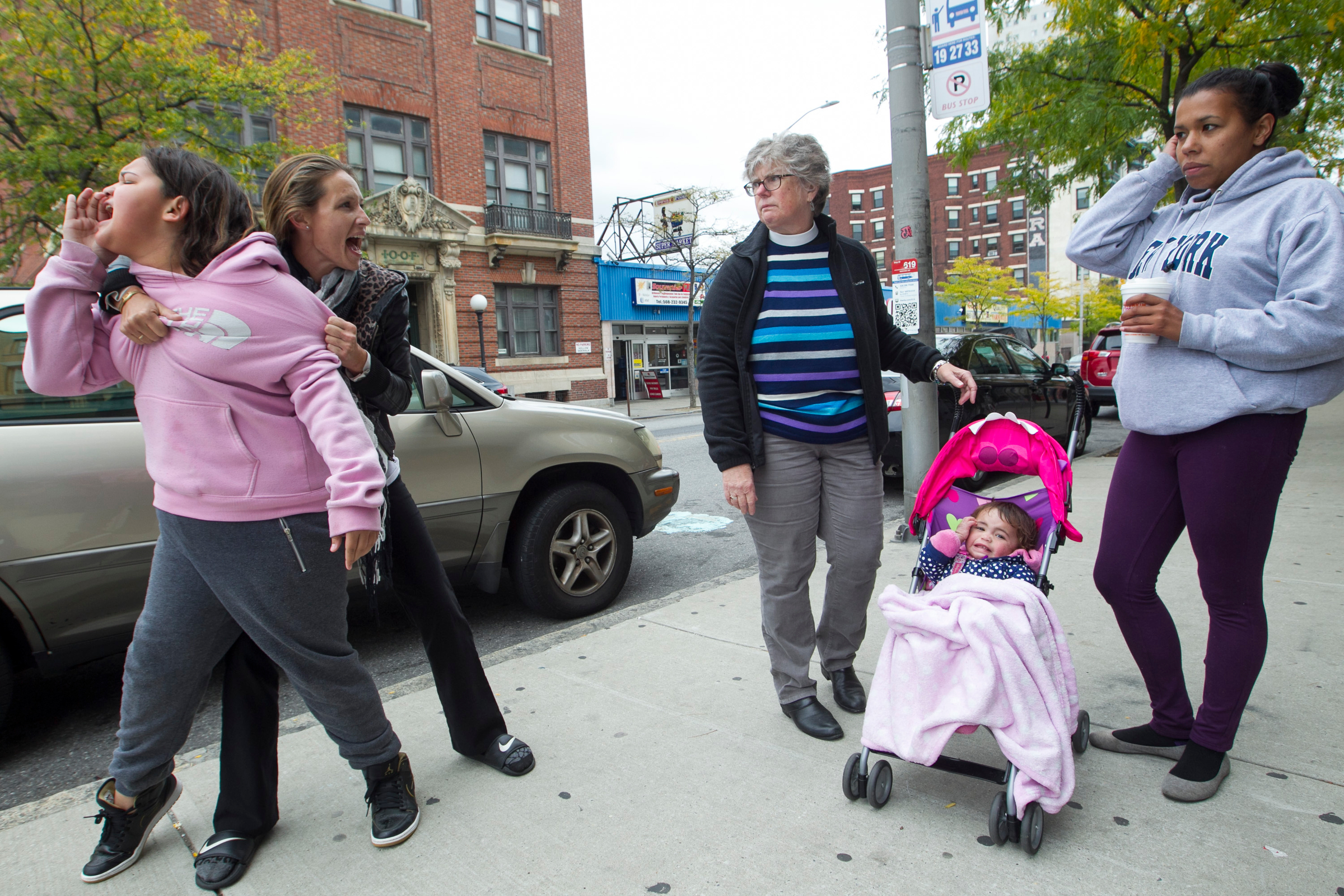 Jill Corso (2nd-L) yells to friend Lesley Cruz (R) as she holds her 12-year-old daughter Arianna Desiderio away from a possible altercation as Urban Missionary Reverend Meredyth Ward (C) stands by Cruz's 16-month-old daughter Xyannaliz Cruz on Main Street in Worcester, Massachusetts on September 30, 2016. Corso and daughter Arianna are currently homeless and staying with Cruz in Worcester.