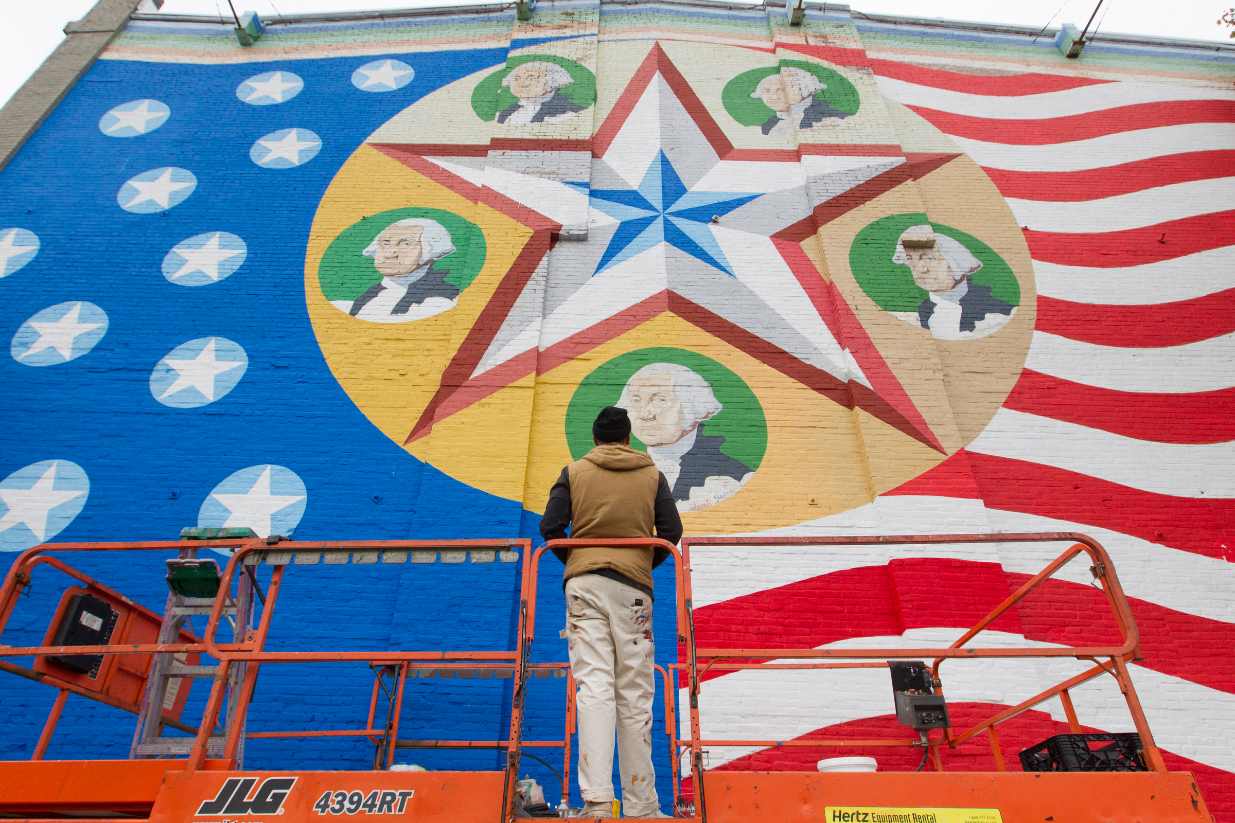 New York City-based muralist and artist Nick Kuszyk works on the restoration of the George Washington Bicentennial Mural on the back of a building on Main Street in Worcester, Massachusetts on October 29, 2016.