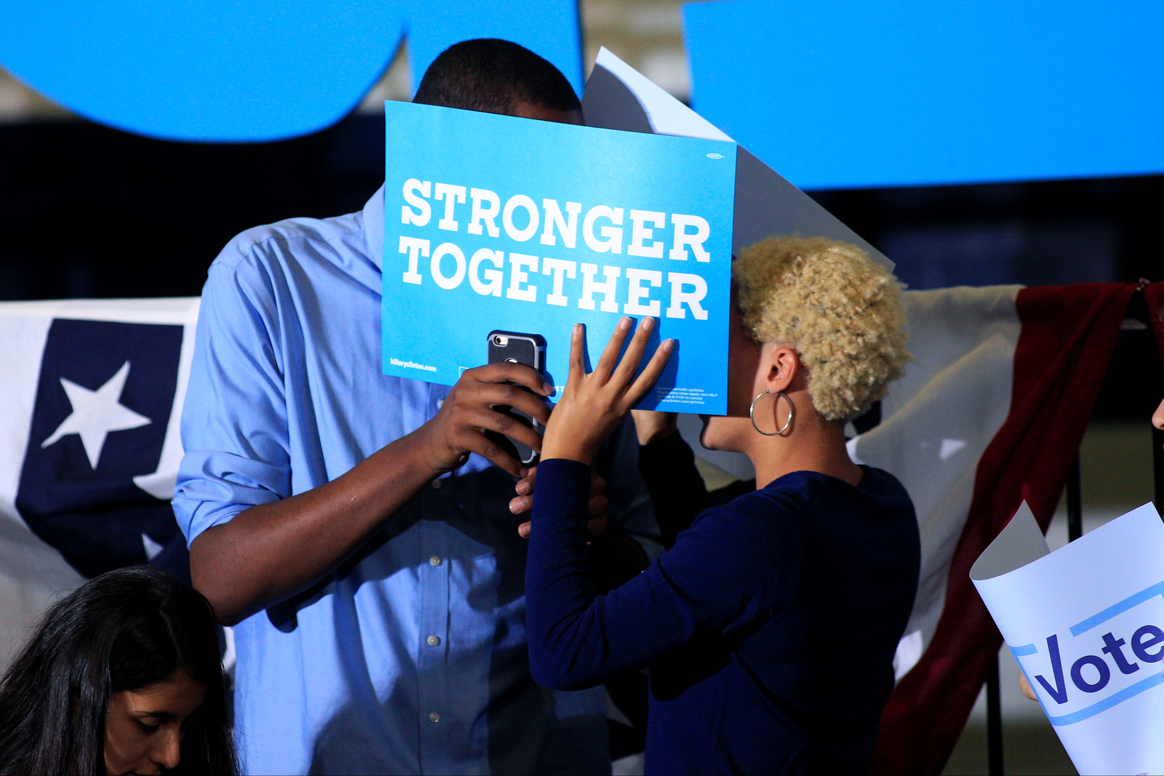 Two supporters of Democratic presidential nominee Hillary Clinton hide behind a campaign sign before the candidate speaks at a rally promoting her college tuition plan at The University of New Hampshire in Durham, New Hampshire on September 28, 2016.