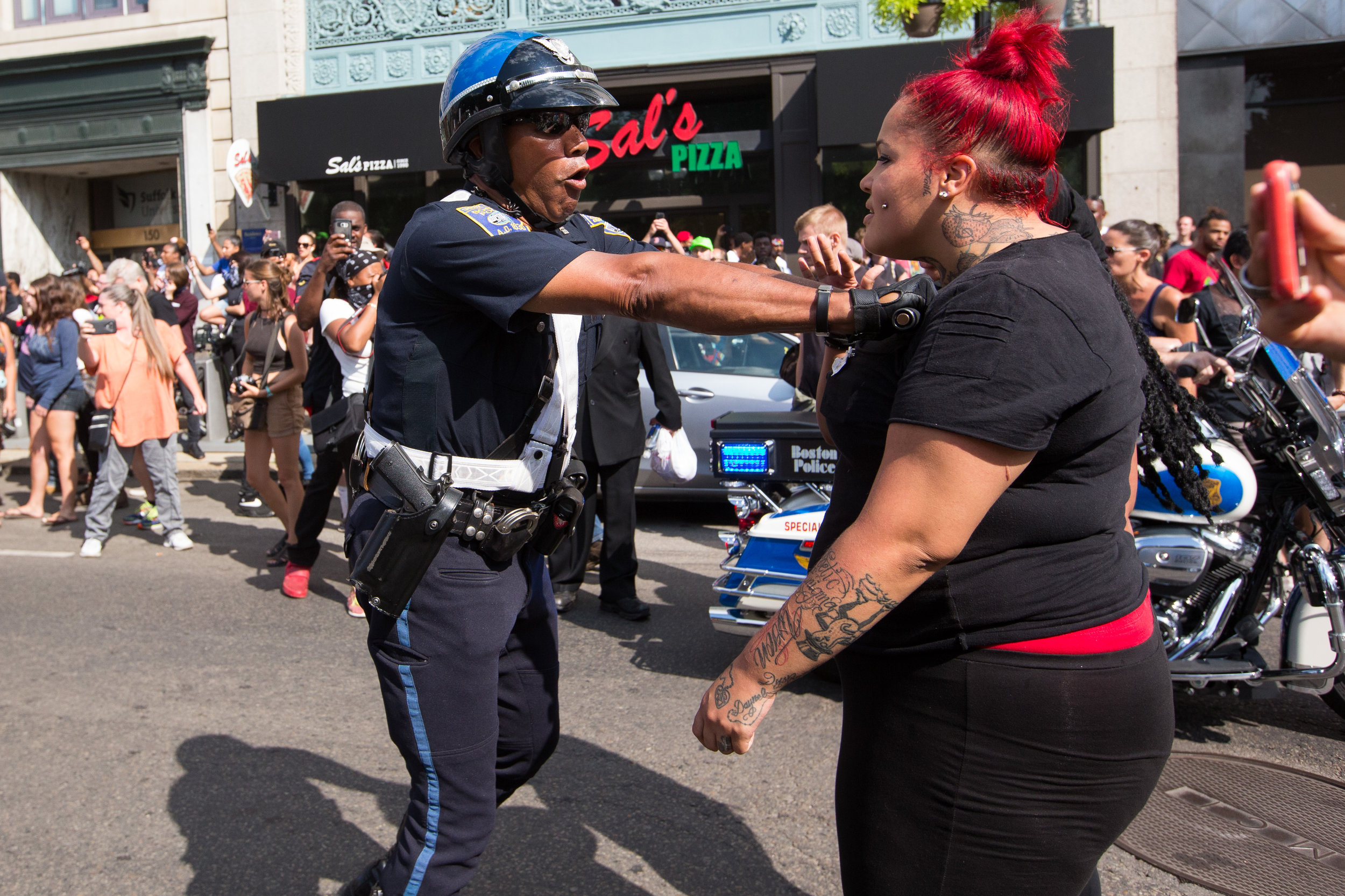 A Boston Police officer pushes back counter-protesters on Boylston Street in Boston, Massachusetts on August 19, 2017. The counter-protesters were gathered in response to an 'alt-right' 'Free Speech' rally.