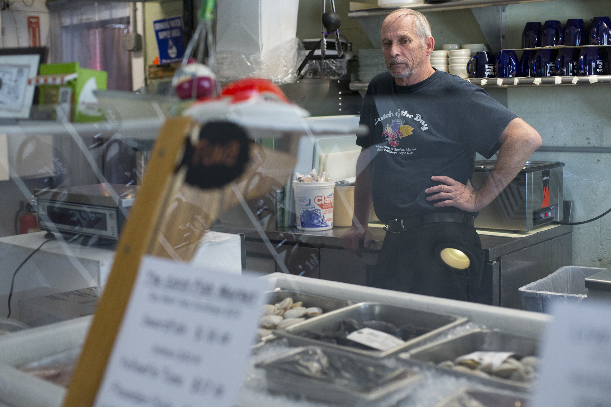Chuck Fletcher, manager of Catch of the Day restaurant and seafood market, takes a quick break behind the counter of the seafood market in Wellfleet, Massachusetts on May 21, 2018. The business is one of many that are having difficulty finding seasonal workers to hire now that fewer visa's for foreign workers are being issued.