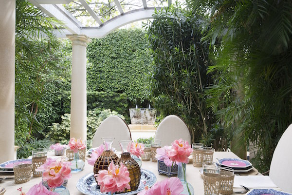 The Slatkins serve lunch on the terrace with hibiscus blossoms from their garden decorating the table.