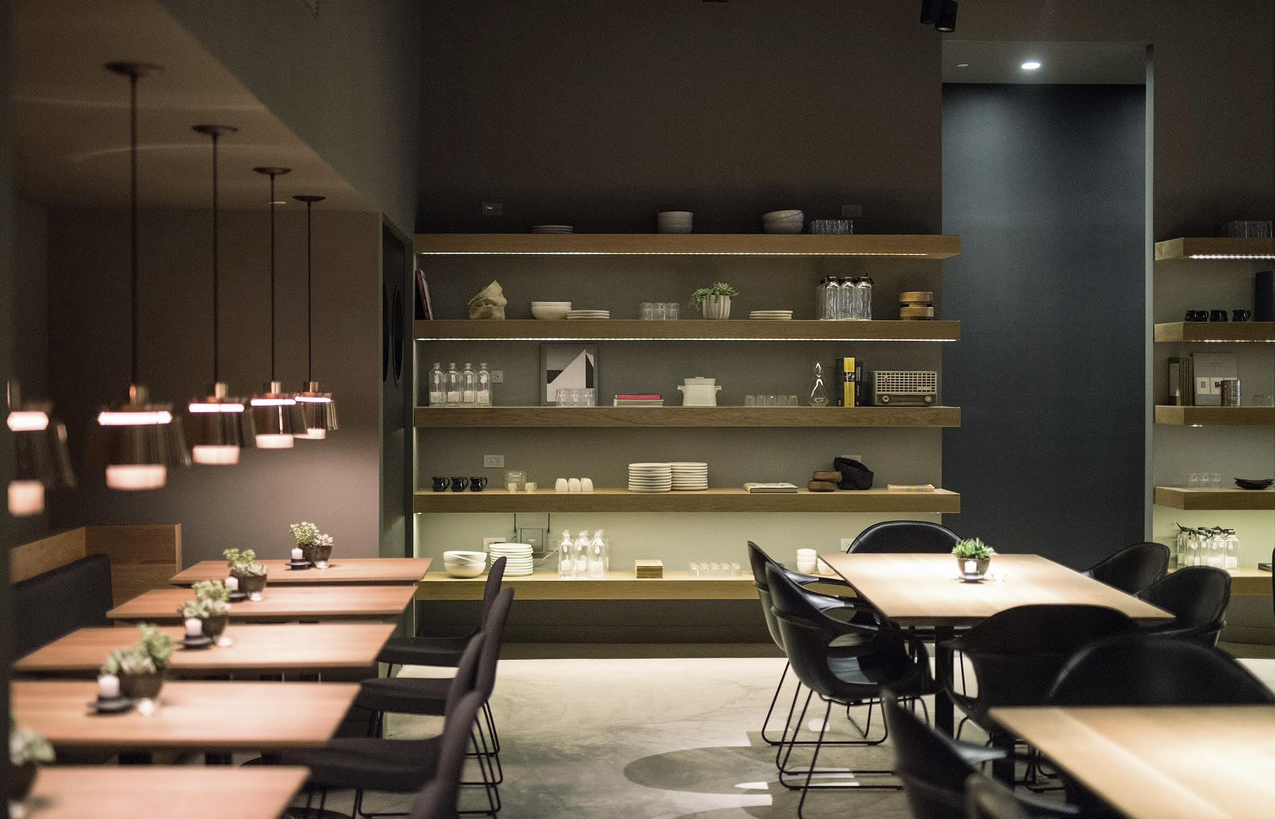 Situated in the Flatiron neighborhood in Manhattan, Cosme's Interior design is contemporary rustic chic, comprising of unadorned wooden tables, poured cement floors, low hanging pendant lights and pleasing vignettes of crockery and barware accessories displayed on open shelves