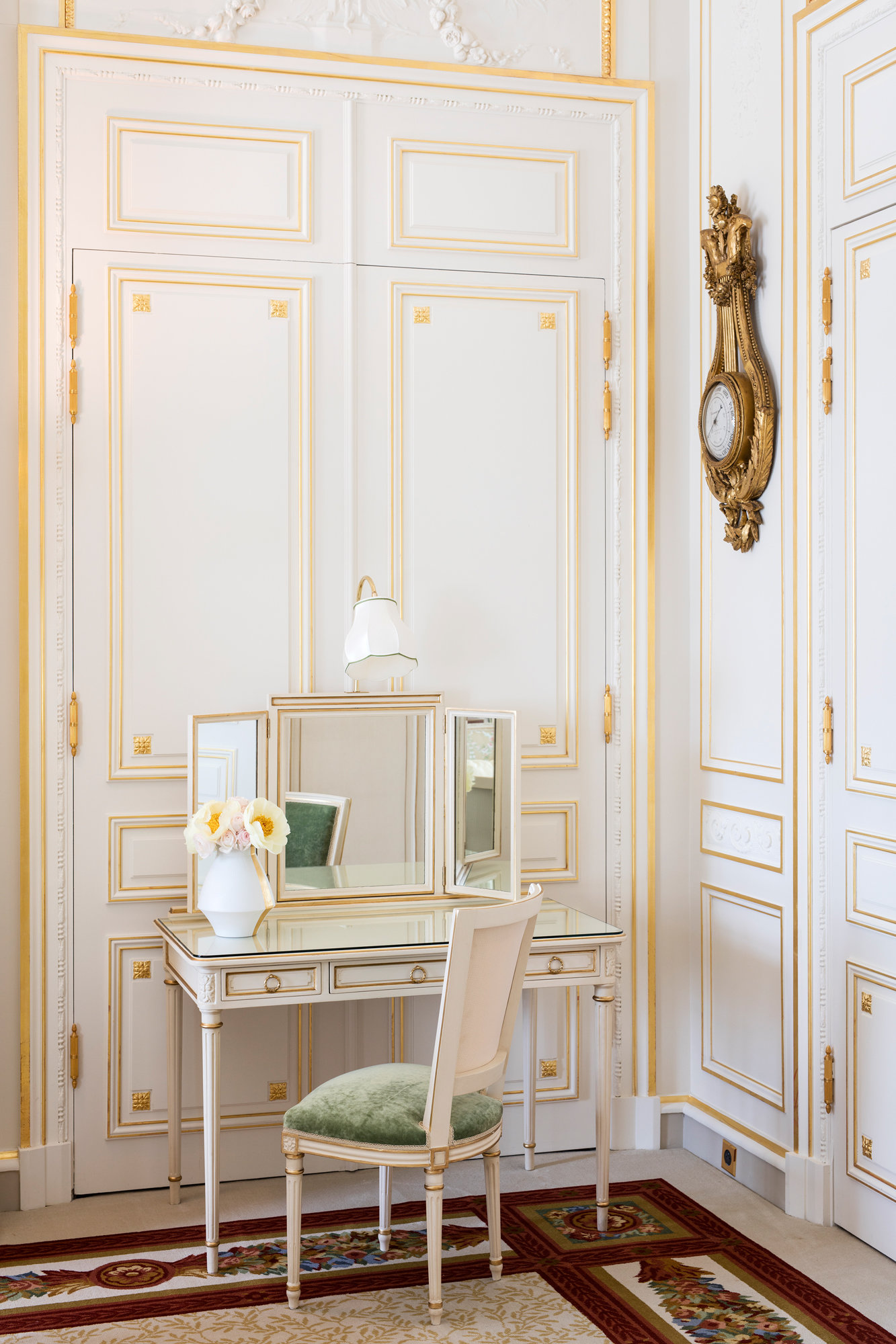 Painted white wooden panels detailed with gold leaf and hardware make this a timeless dressing area