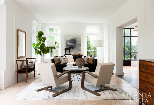Wood framed seating and cabinetry make a vivid contrast with the white walls, while maintaining a zen vibe