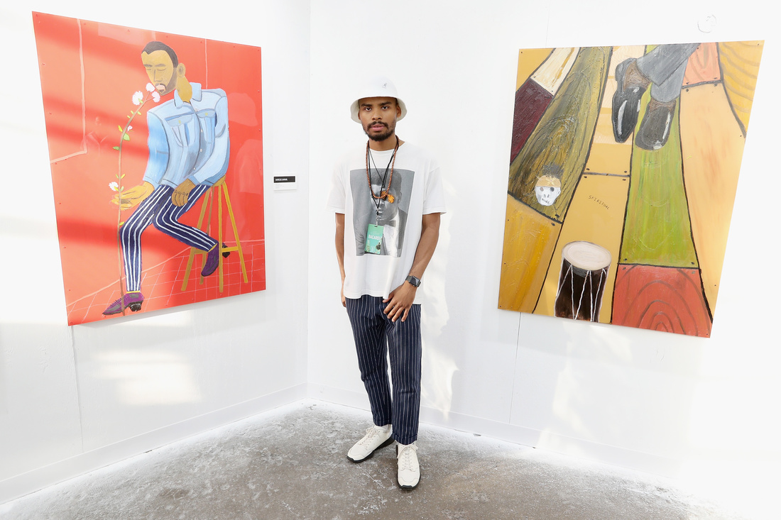 """Artist Marcus Jahmal with his paintings at """"No Commission"""" -  Photo by Angela Pham"""