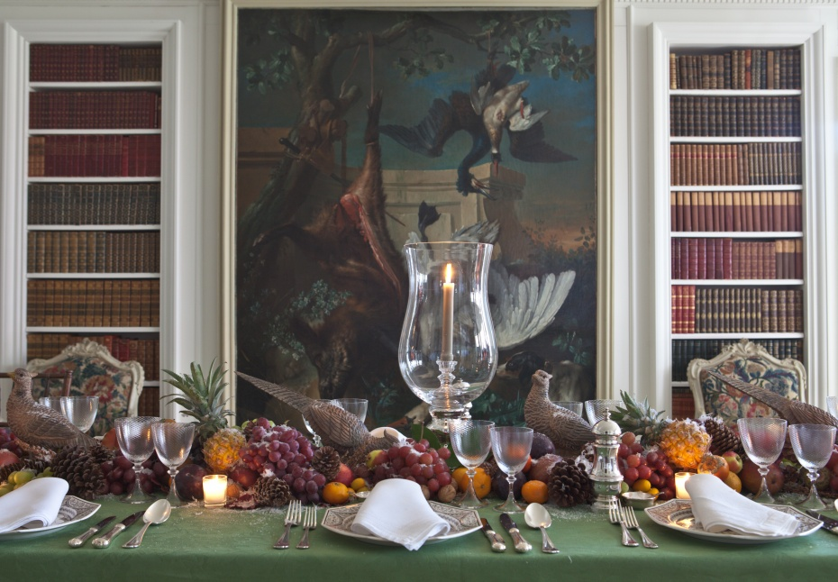 Carolyne Roehm's Thanksgiving table laden with an abundance of fruits and bird figurines -the intense artwork with a scene of diving birds makes for a dramatic backdrop