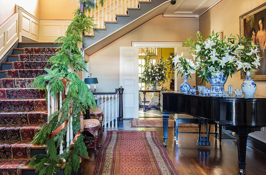 A grouping of Chinoiserie vases offset the lush stair garland and white florals