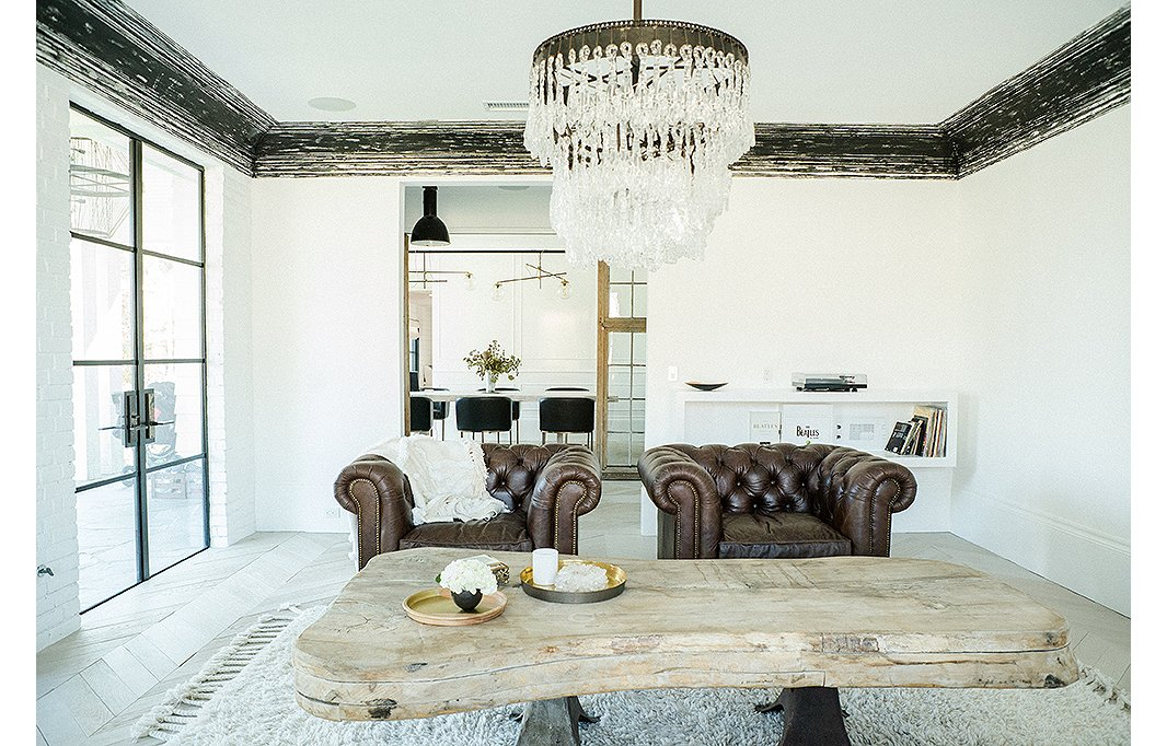 A warm minimalism room with added sparkle from a crystal chandelier -  photo by   Josh Franer    One Kings Lane